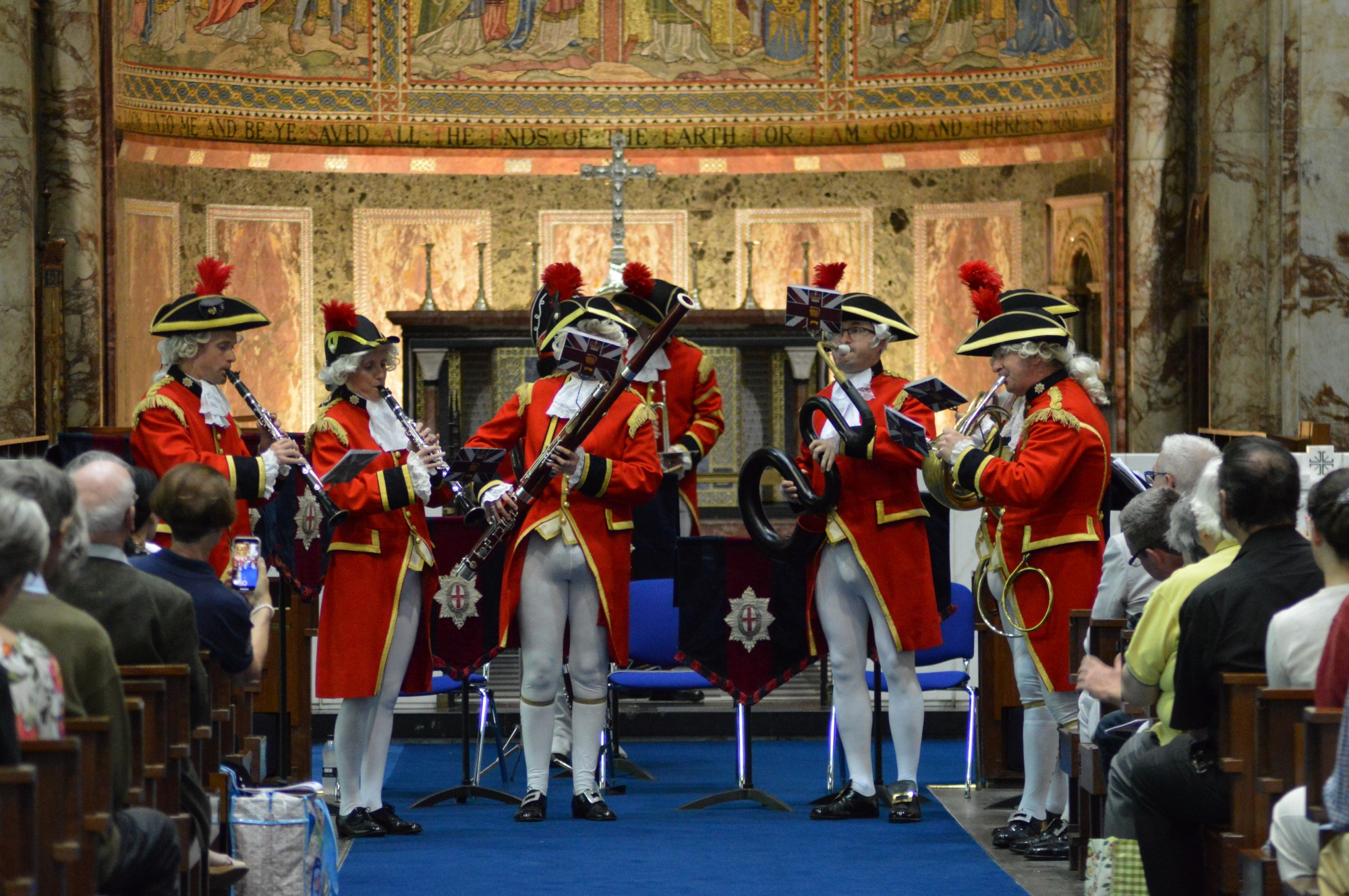 Men dressed as British soldiers playing in a band in a sancturary in front of a seated audience.
