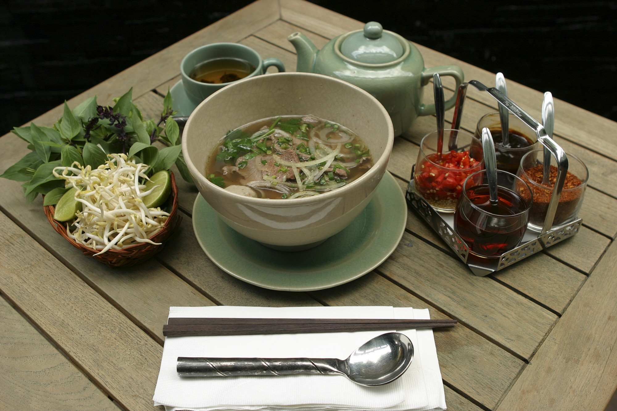 Bowl of pho surrounded by beansprouts and sauces