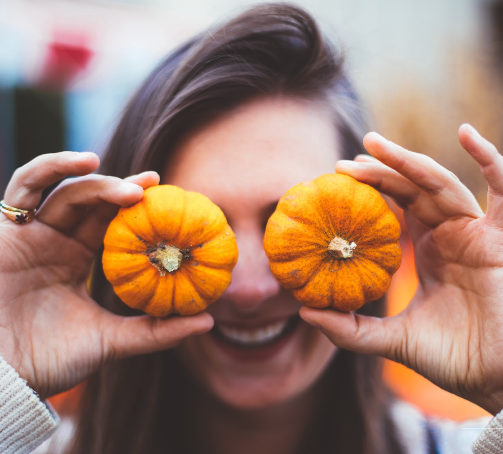 Smiling woman holding two small pumpkins in front of her eyes.