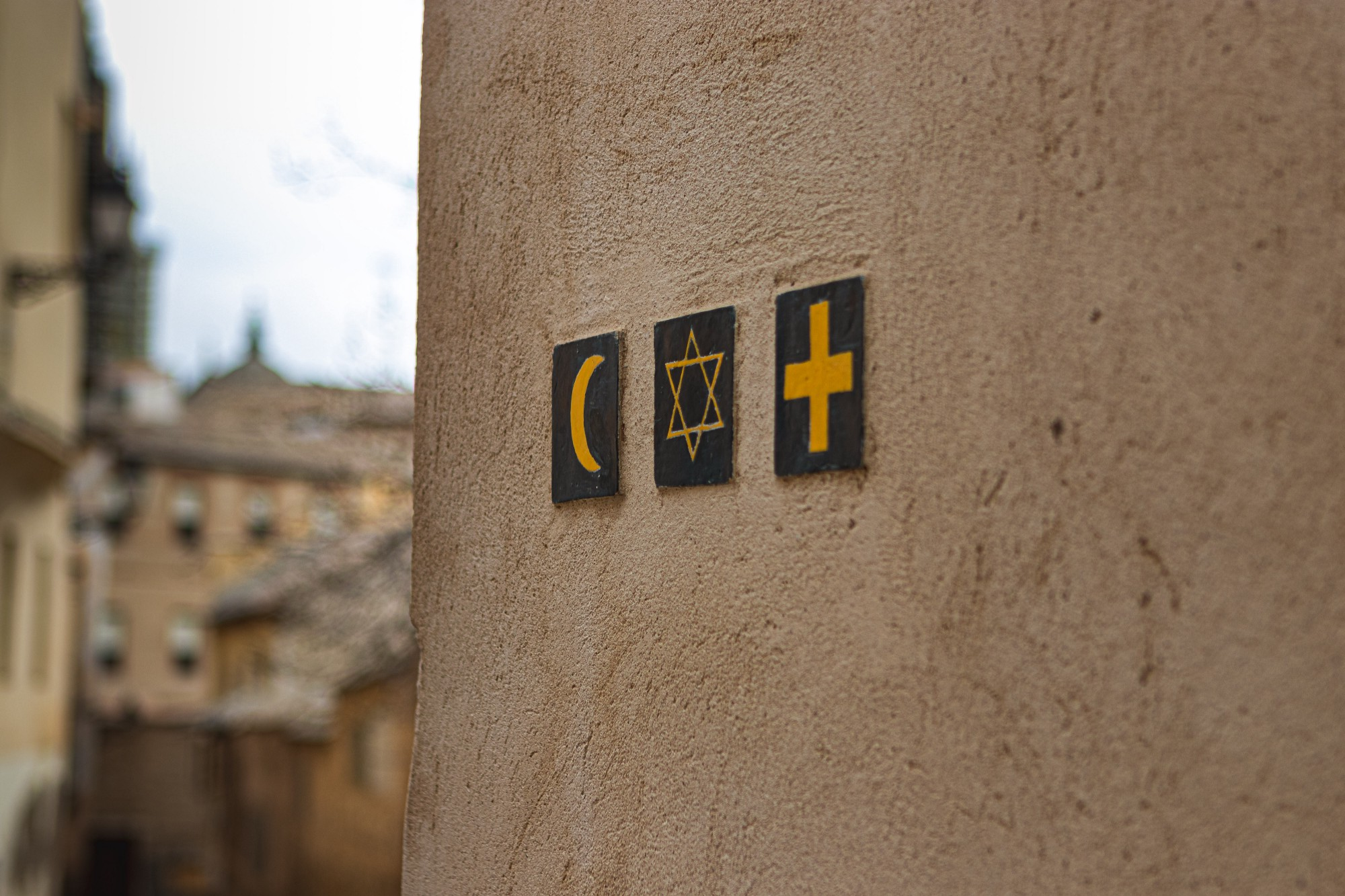 The crescent moon symbol of Islam, the star of David symbol of Judaism, and the cross symbol of Christianity on the side of a brown, mud wall.