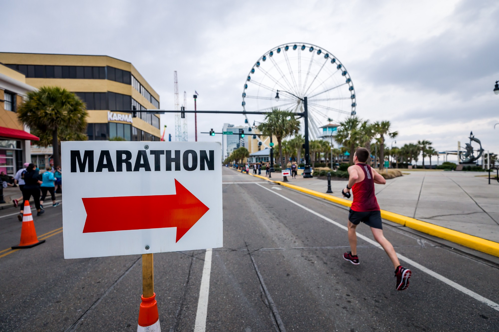 Runner running past a marathon sign with a red arrow