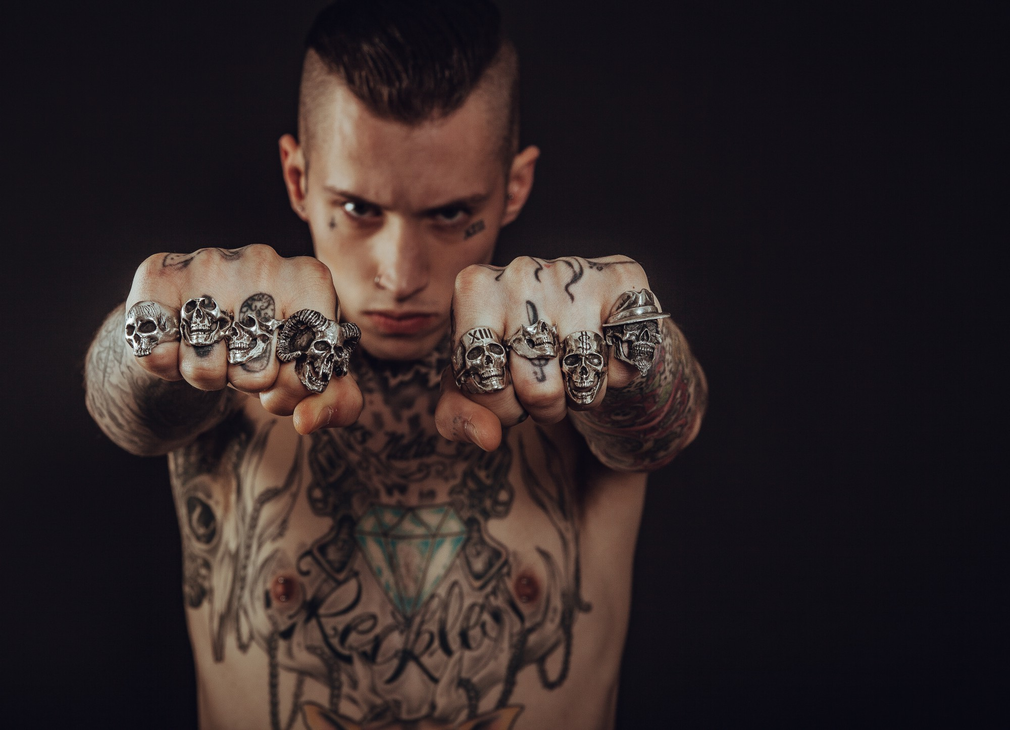 Shirtless man with tatoos making fists and wearing skull rings on all fingers.