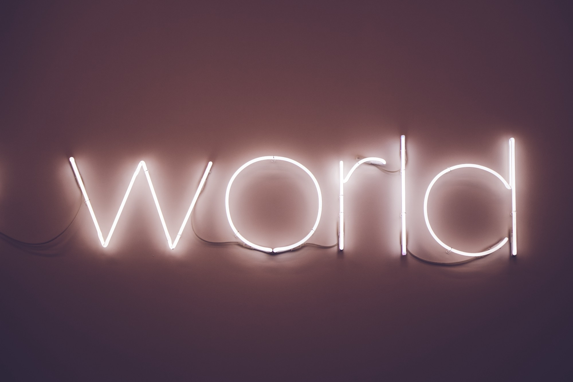 "neon sign surrounded by darkness reads ""world"" in a faint purple."