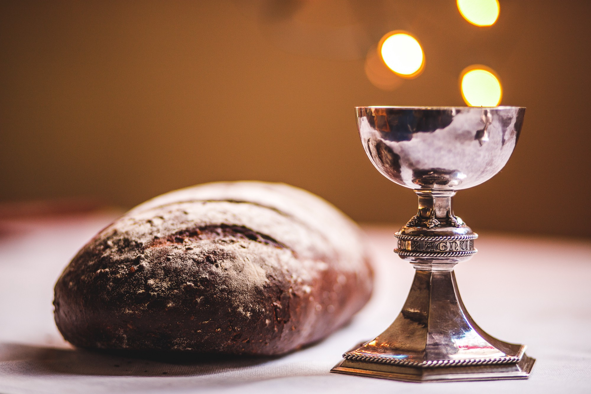 Holy Communion bread and wine in a beautiful gold challis with fabricated bubbles rising from wine to represent life both on light colored wood table with orange tan colored wood on back wall.