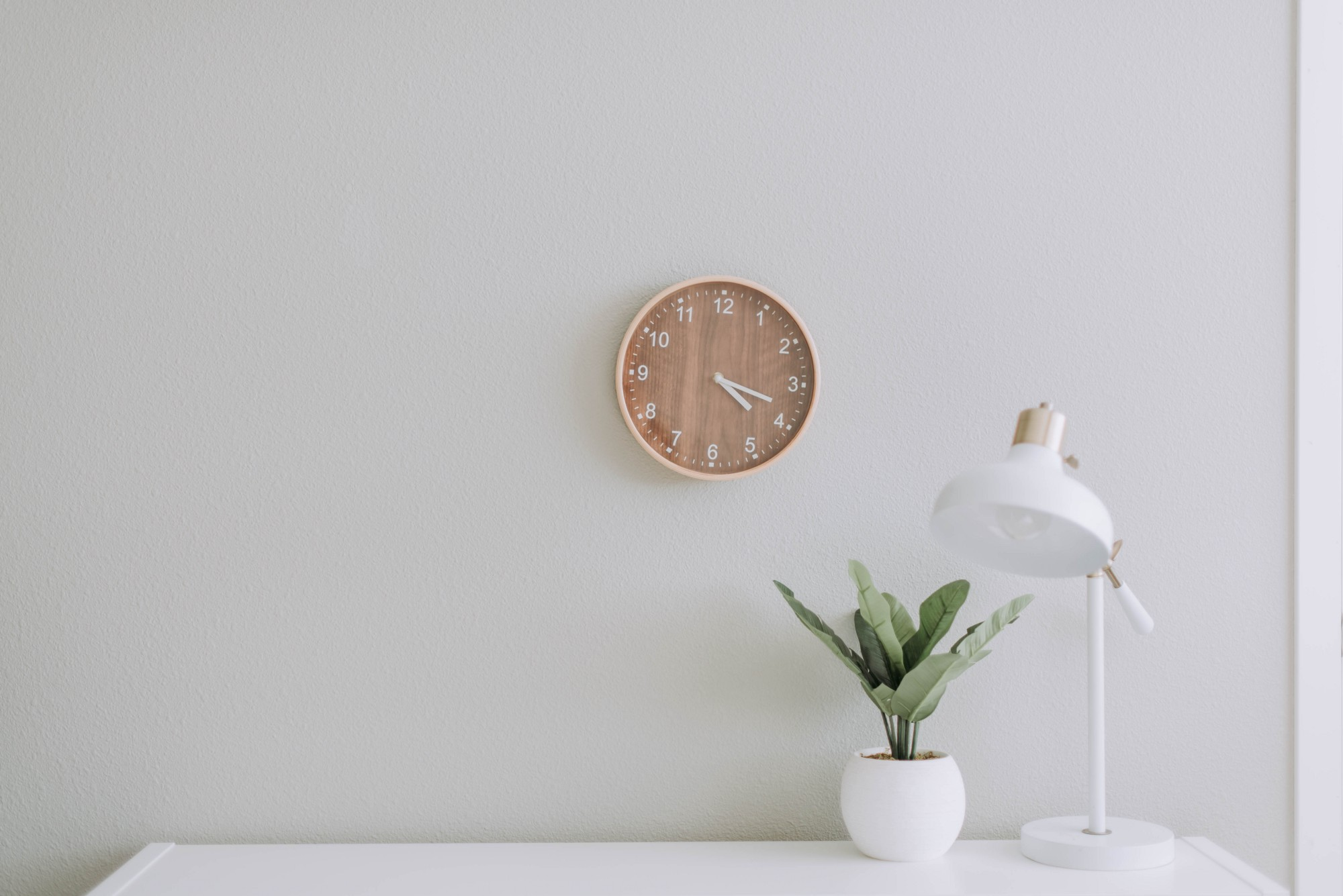 Wooden wall clock over a white desk and plant.