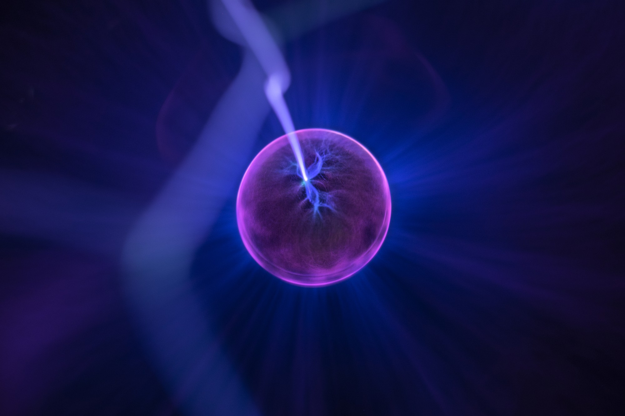 a spark of lightening pierces a purple cylinder in a deep blue background
