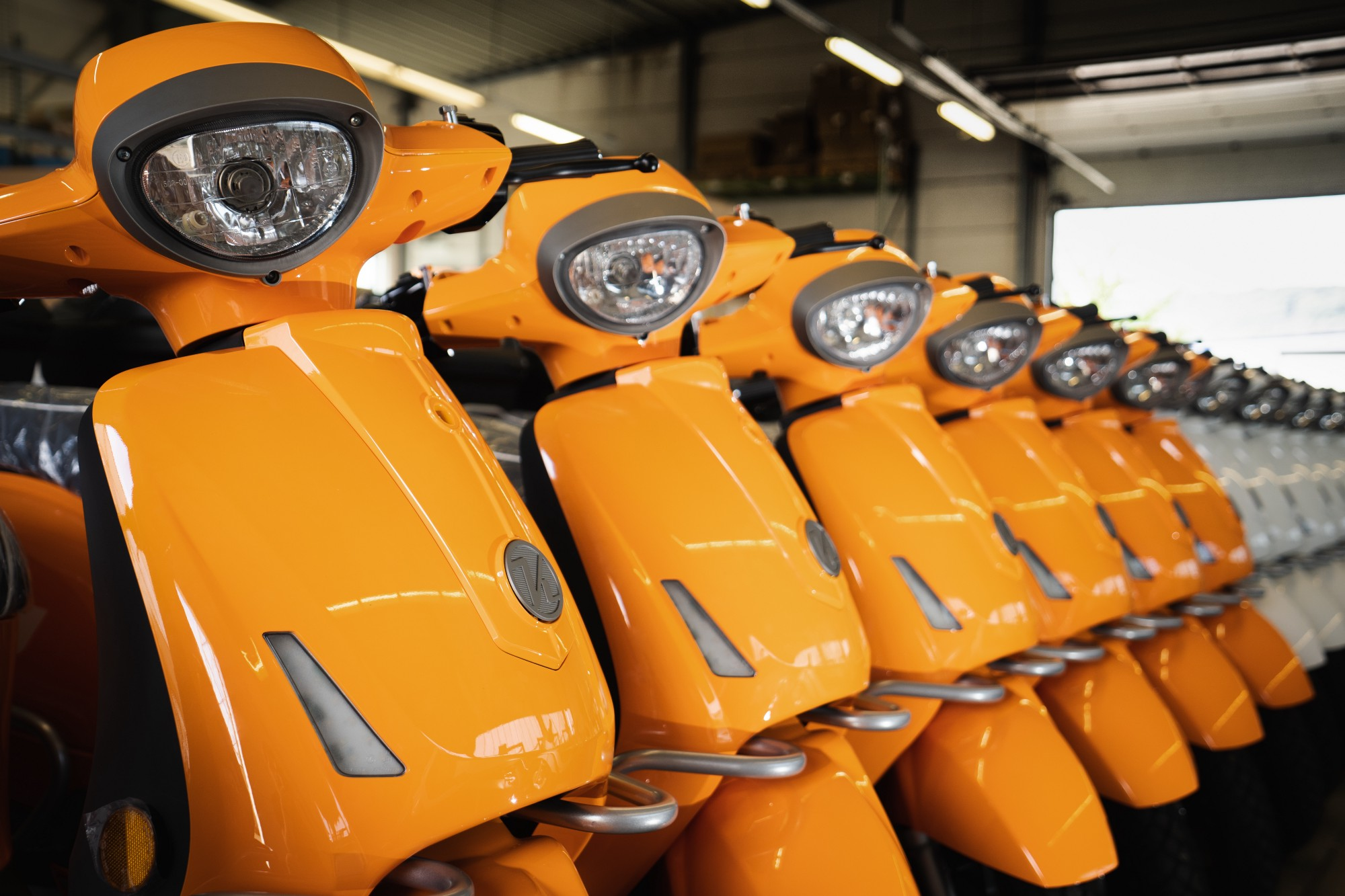 Several electric scooters in line as they go out of the production line.