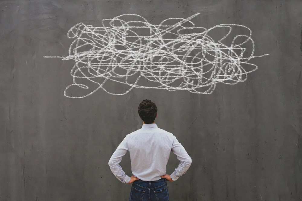 A man looking up at a complex scribble of chalk line drawing