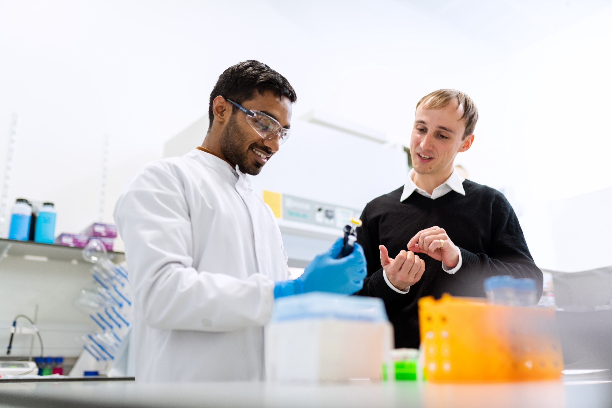 Stock photo of two student scientists in a lab.