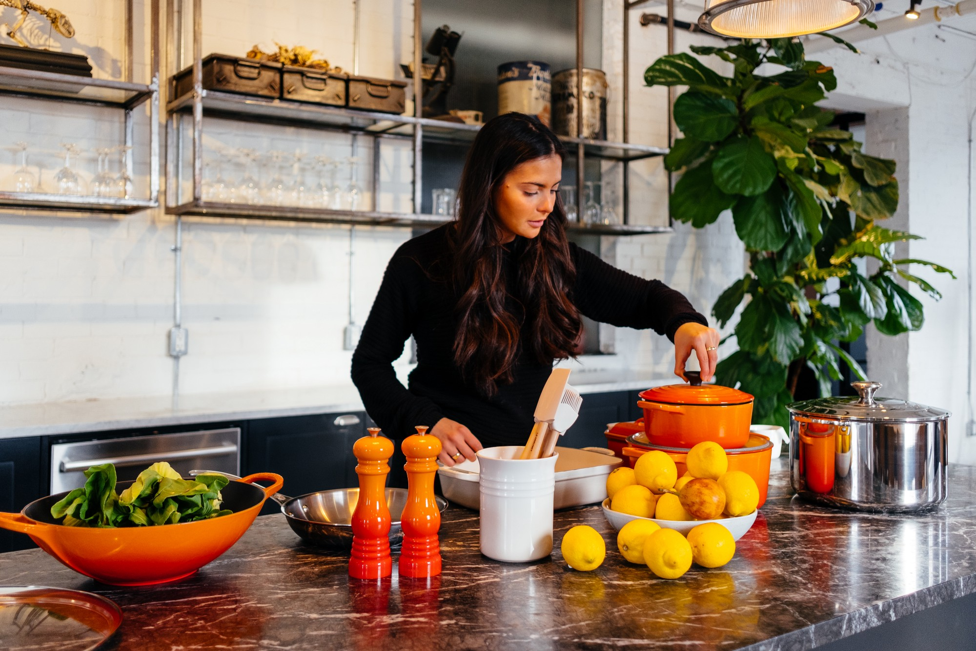 A woman in a kitchen with colourful equipment and a bowl of lemons