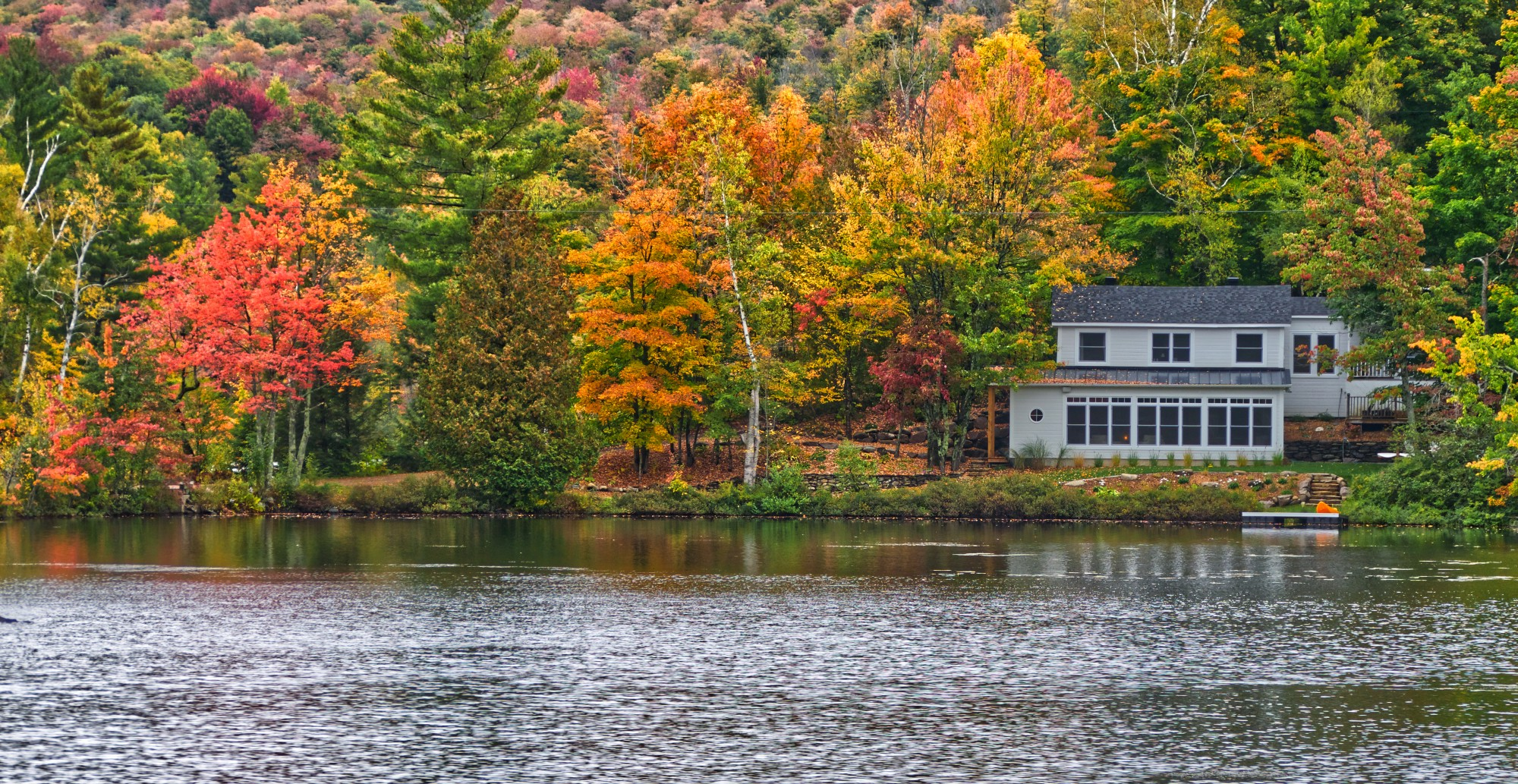 A quiet house by a river or lake with colorful autumn leaves.
