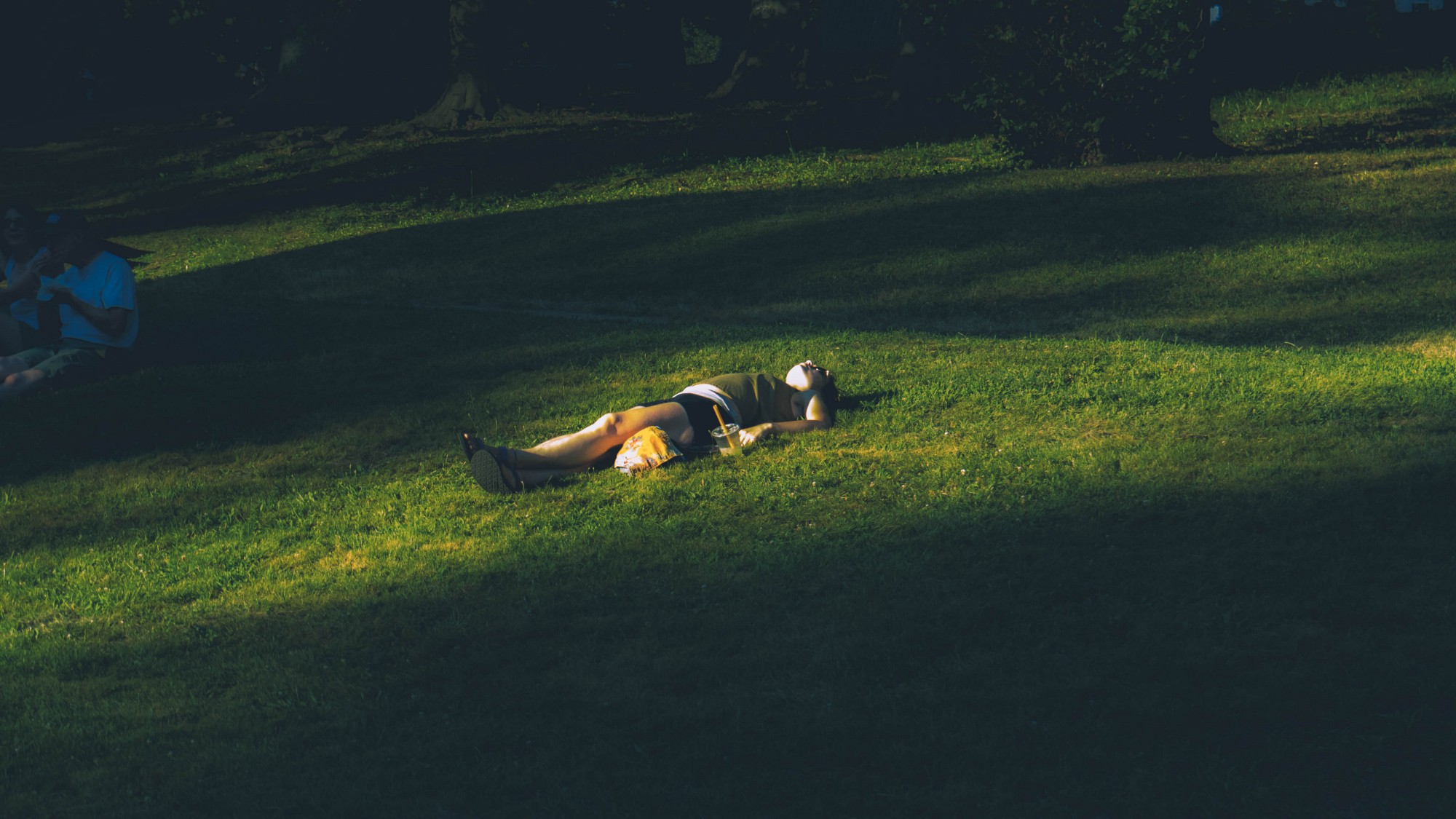 Person laying on their back on a grassy knoll.