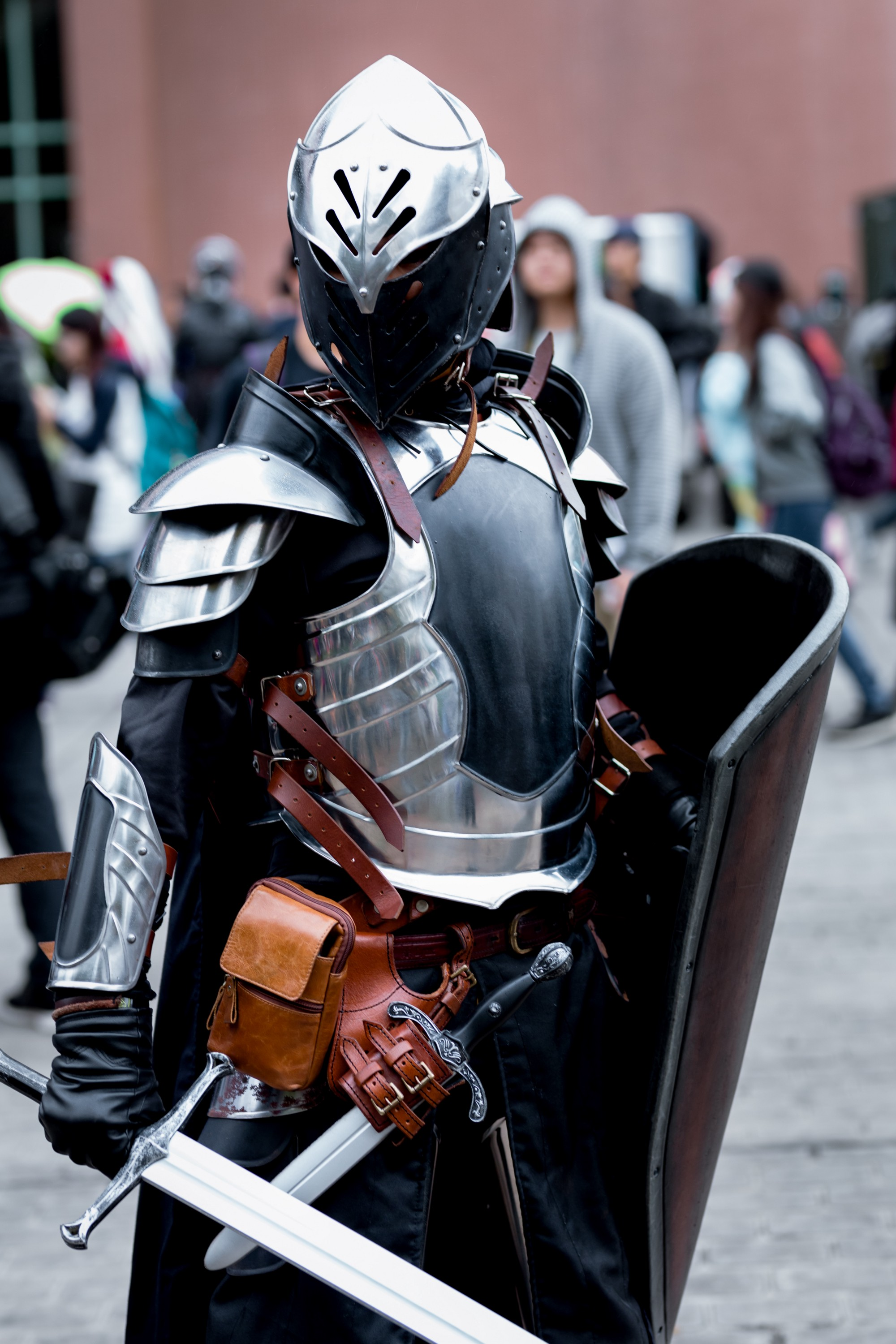 A man standing with armor on and many people behind and beside him.