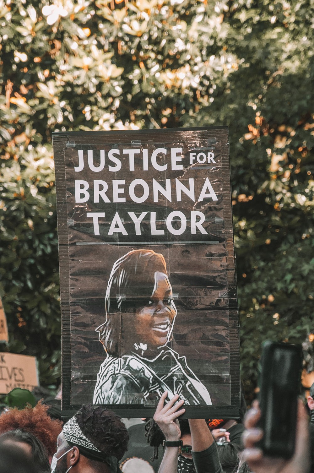 """[ID: a placard from a Black Lives Matter protest with Breonna Taylor's face, which reads """"JUSTICE FOR BREONNA TAYLOR.]"""
