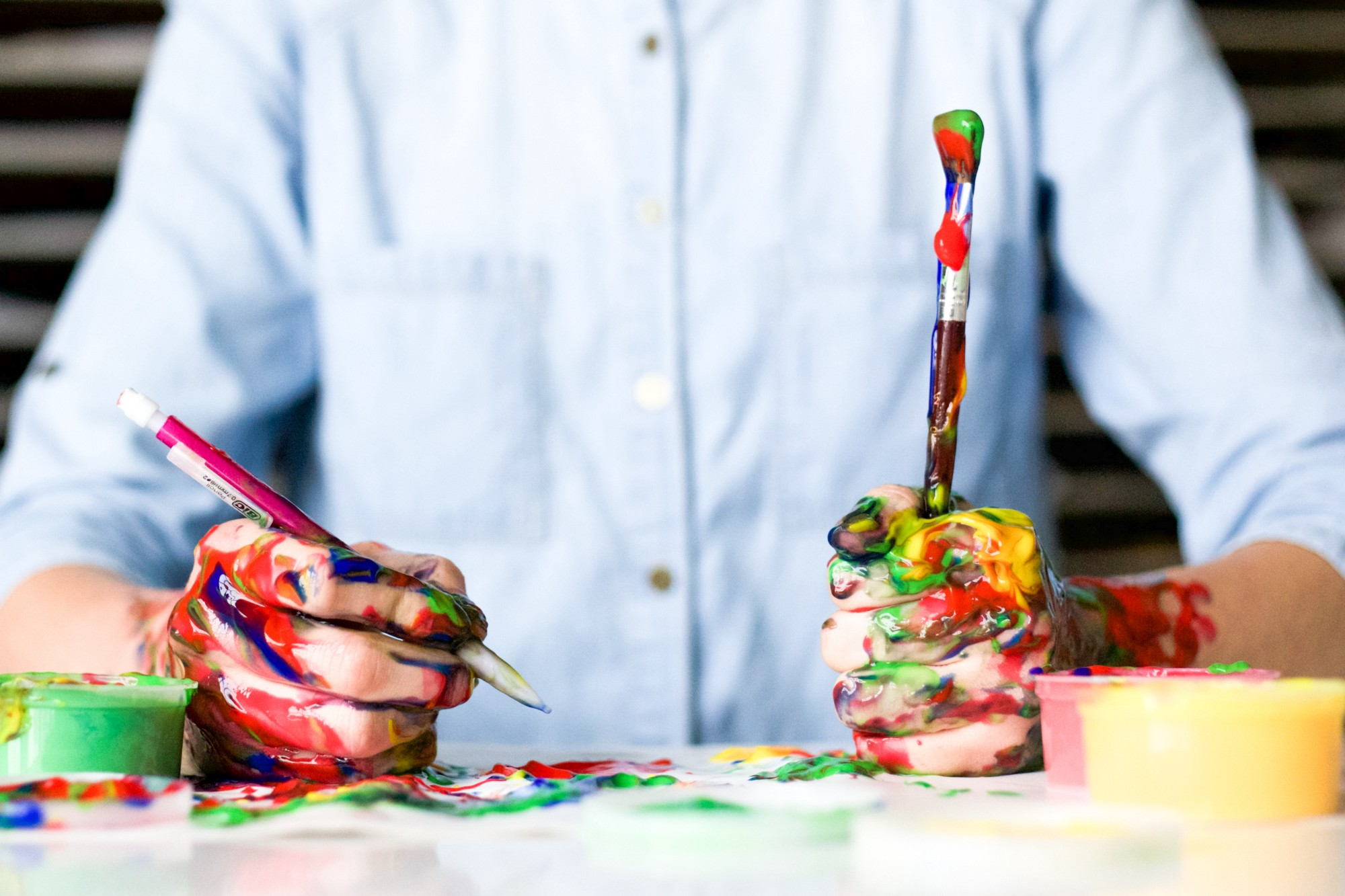 man in a blue button up dress shirt, with paint brushes in one hand and a pencil in the other. Both hands are covered in paint.