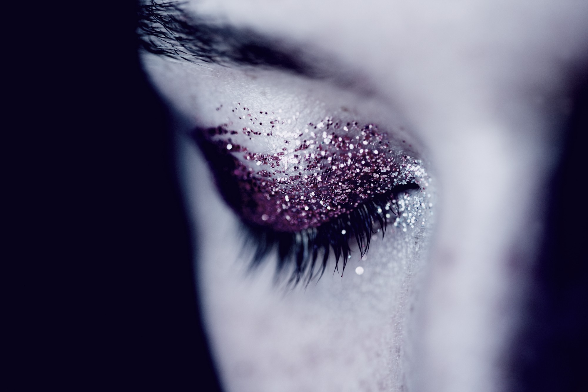 Half a woman's face with a pink glittered eyelid