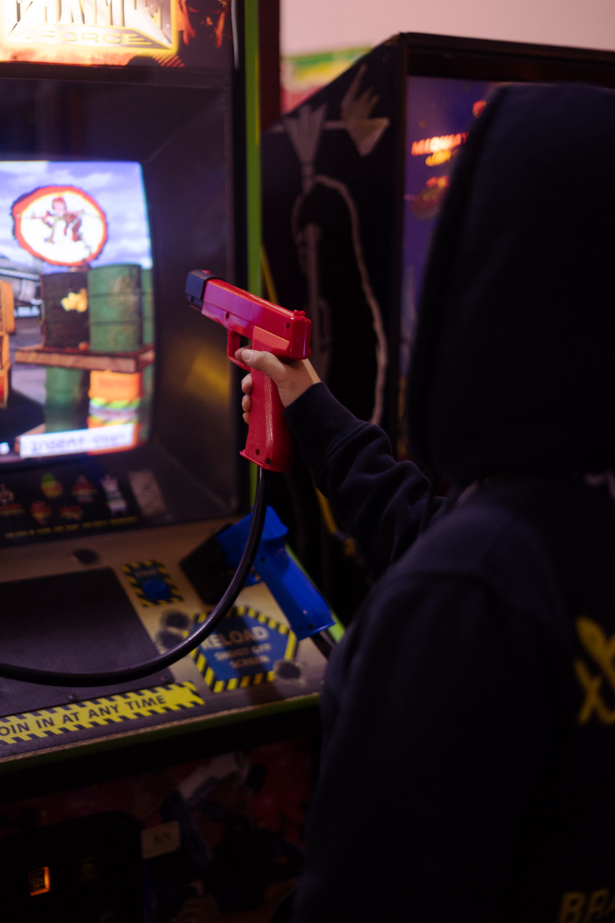 A person playing a shooting game at an arcade cabinet holding a red gun controller pointed at the screen.