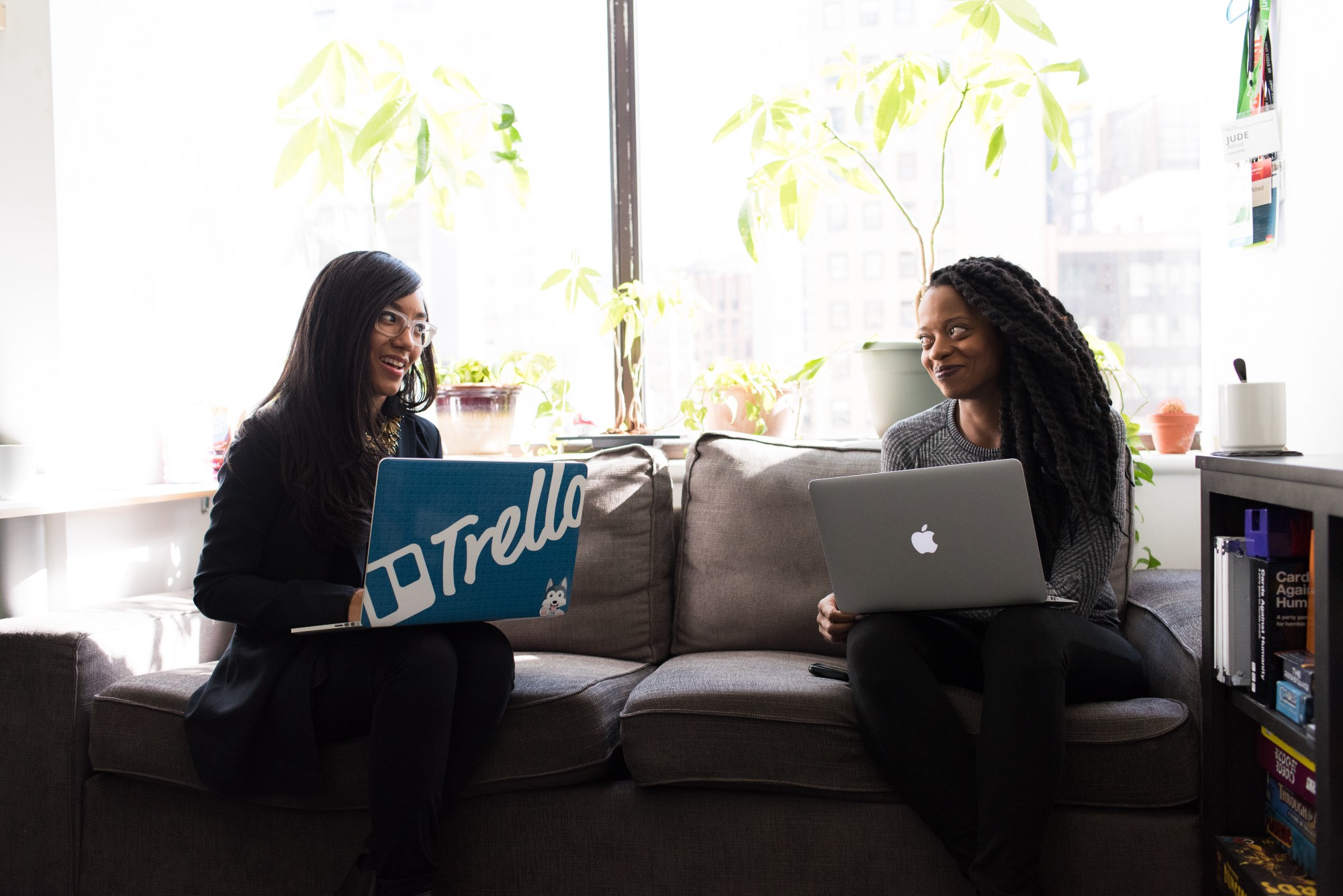 Two women of color smile at each other with open laptops.