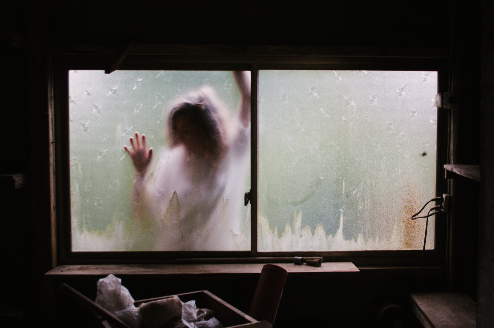 Blurred image of a woman with her hands placed against a window. Spooky, creepy, trapped feeling.