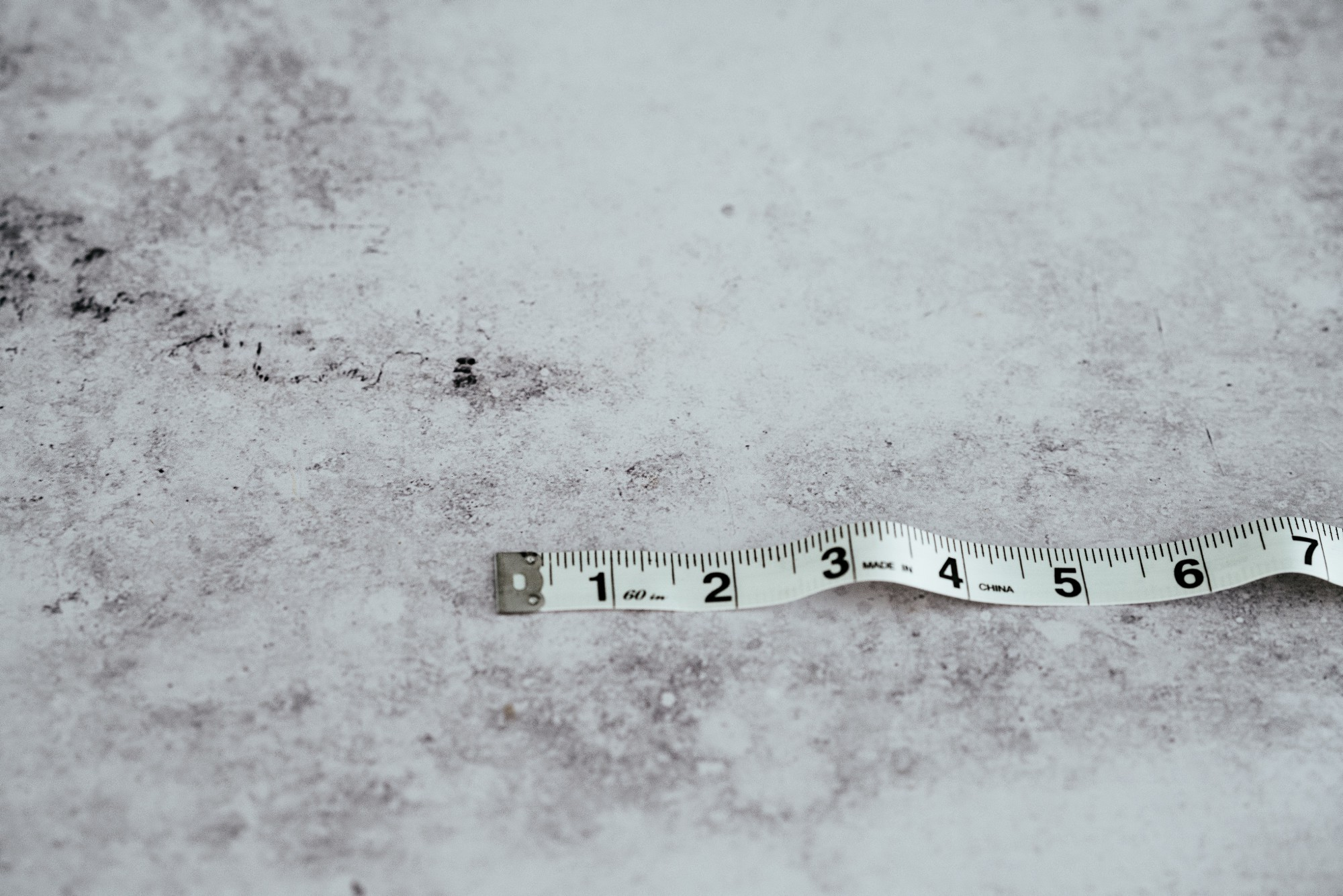 A measuring tape on the gray concrete showing the one through seven inches marks.