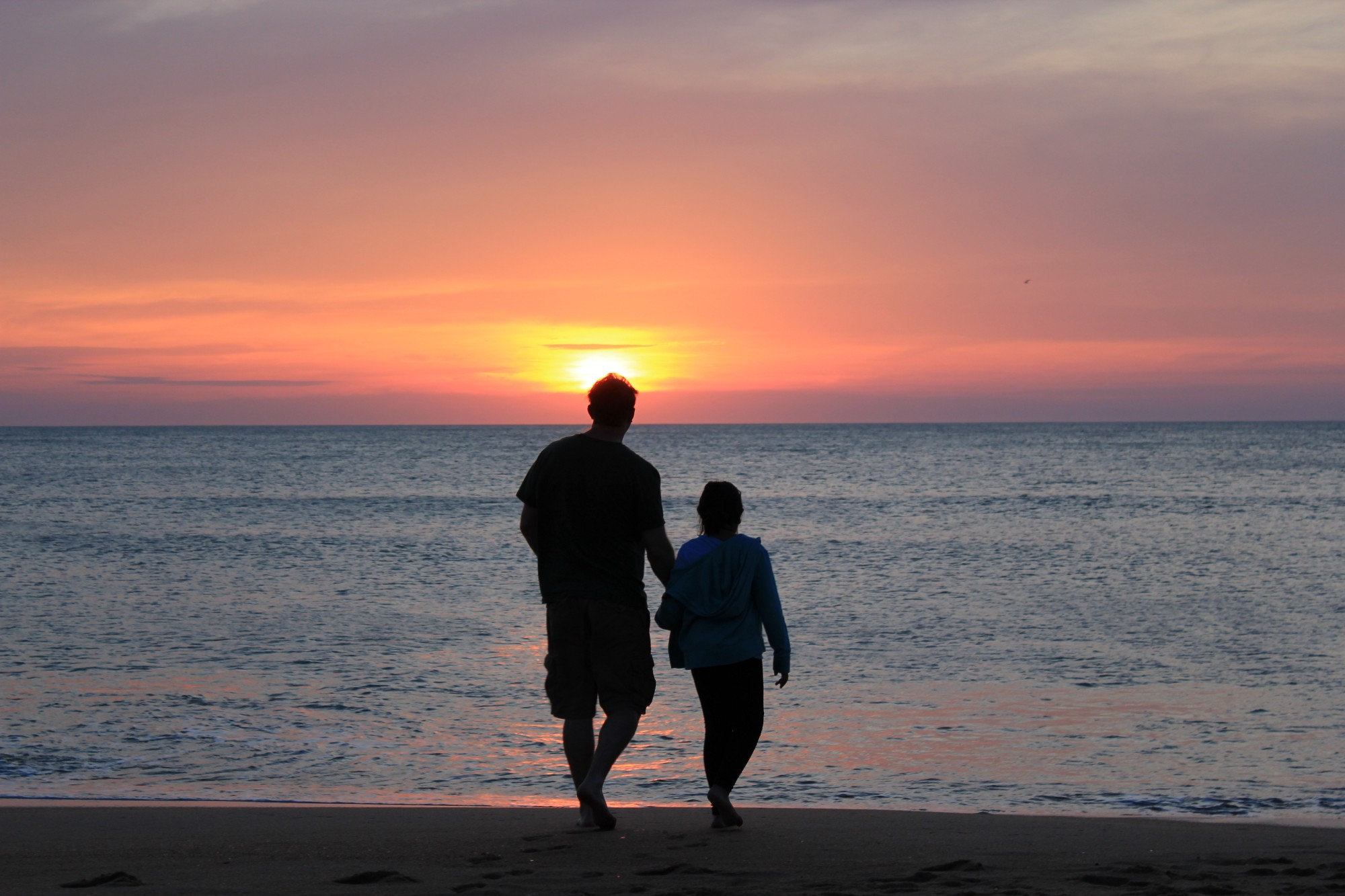 man and girl/young woman walking into a watery sunset with their backs to the camera