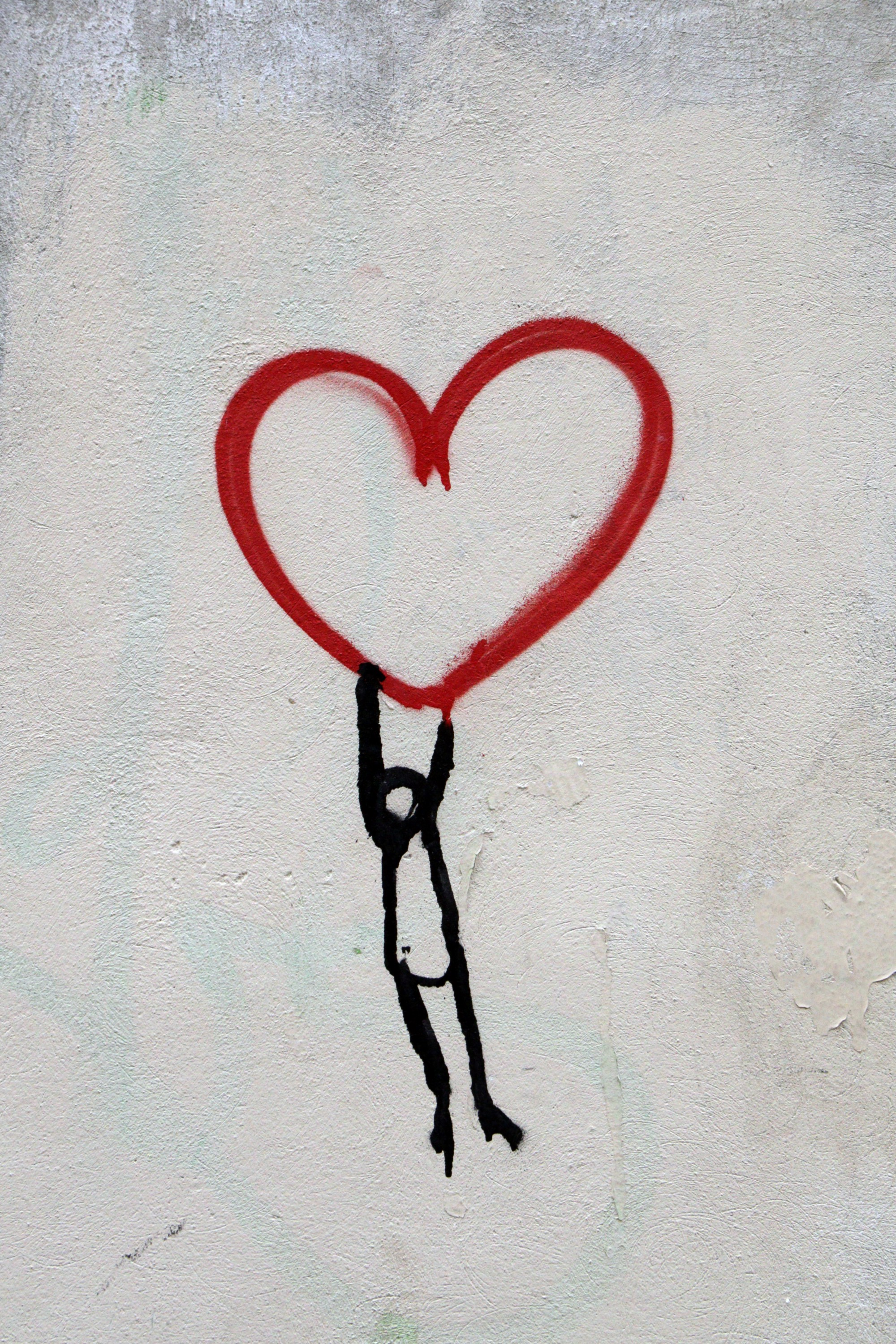 A graffiti painting of a stick man hanging onto a red heart above