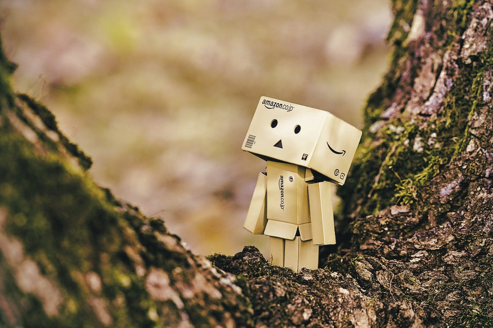 Cardboard robot toy on wooden tree photo