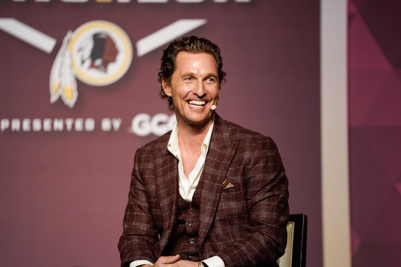 Image of Matthew McConaughey seated on stage at an event.