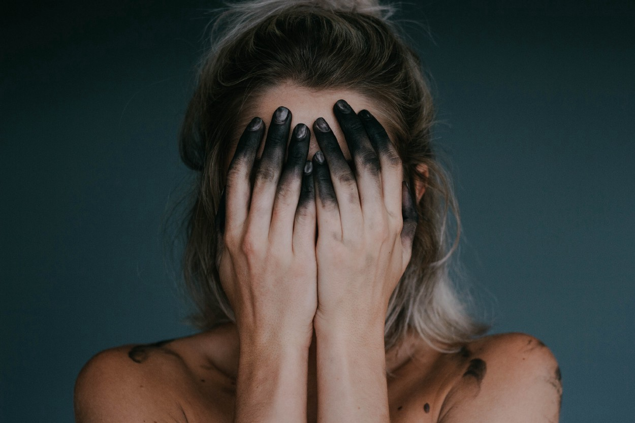 A woman covering her face with her hands, her fingers black as though burnt