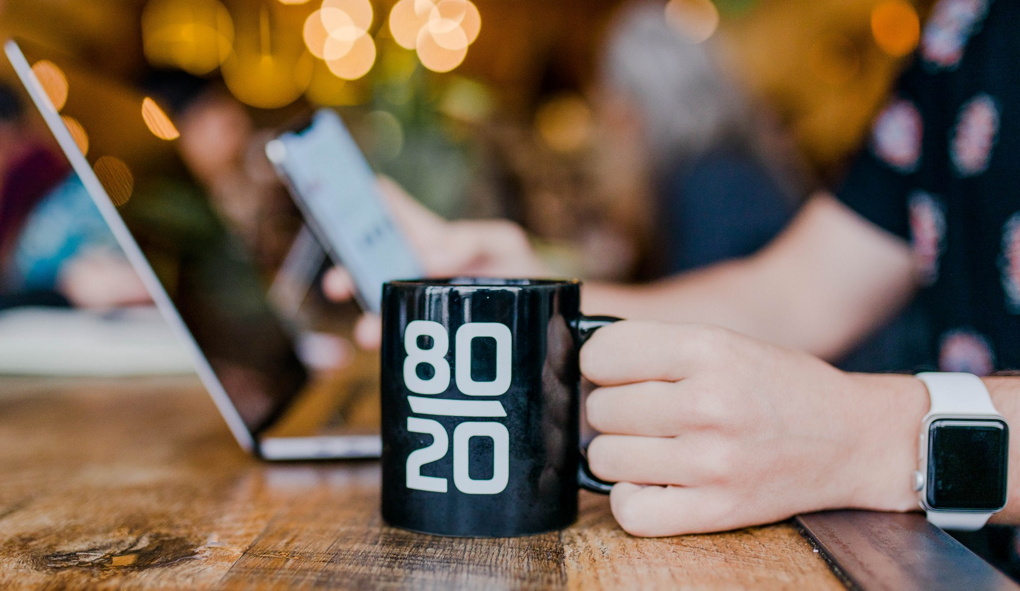 A mug saying 80 20 rule beside a laptop in a cafe