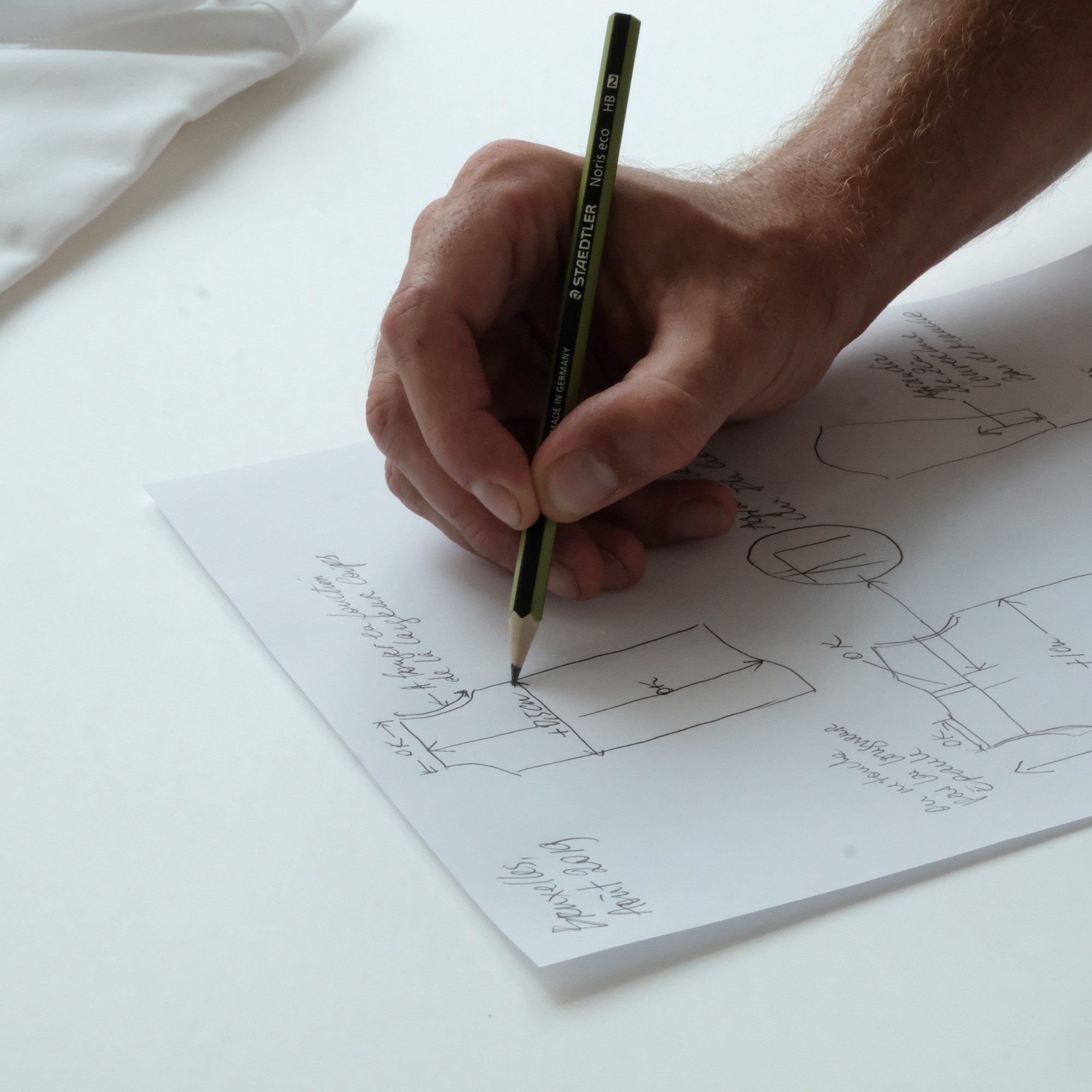 A designer sketching a drawing on paper.