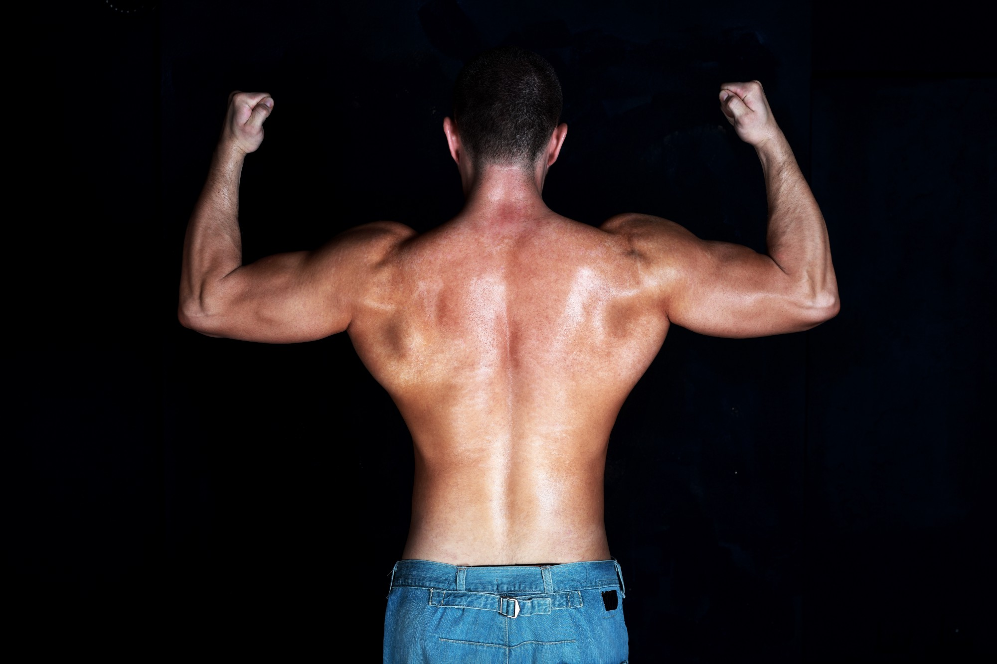Muscles man flexing his muscles with a dark background