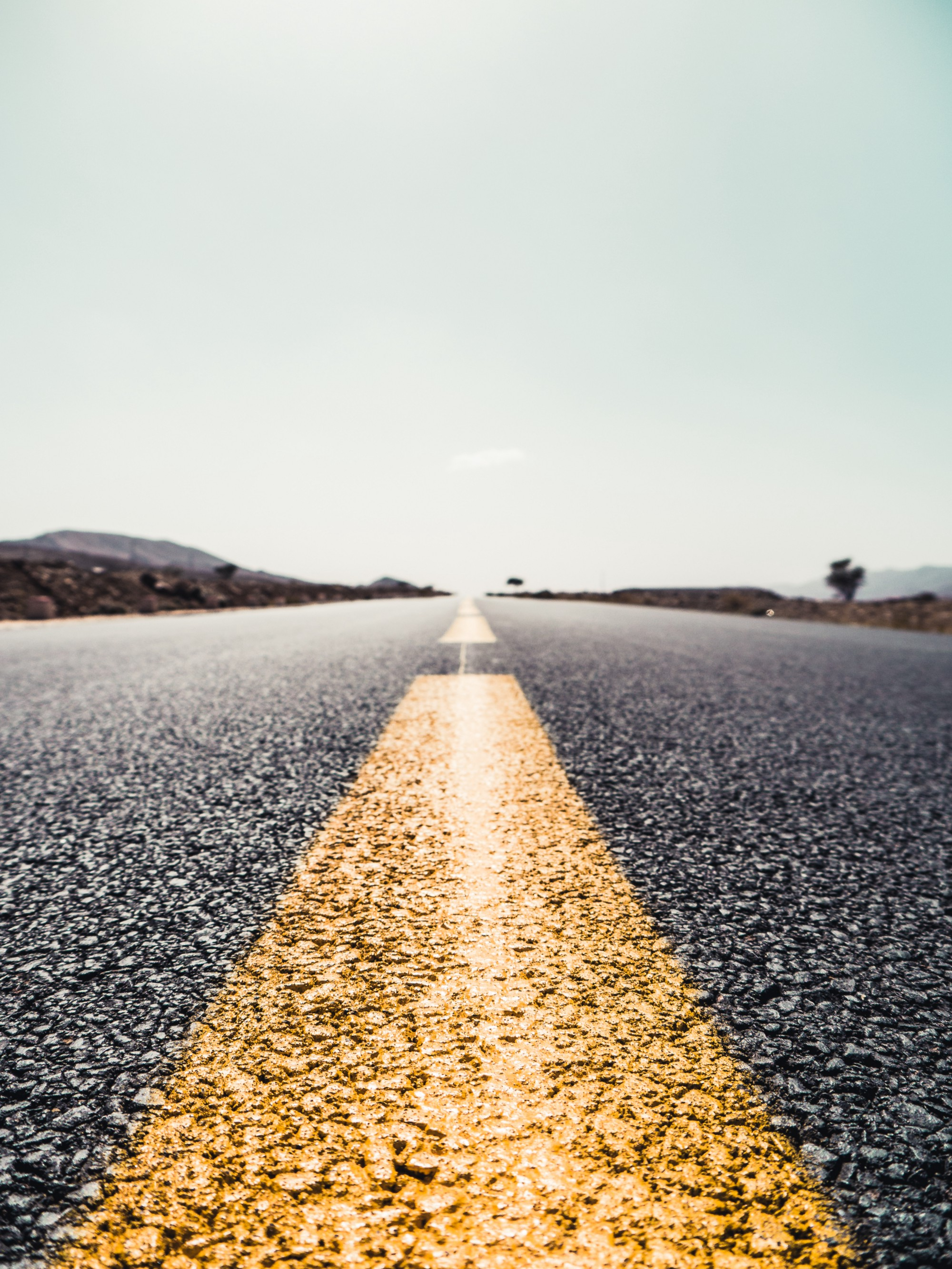 Image of the yellow lines at the center of a long, empty road with mountains on either side.