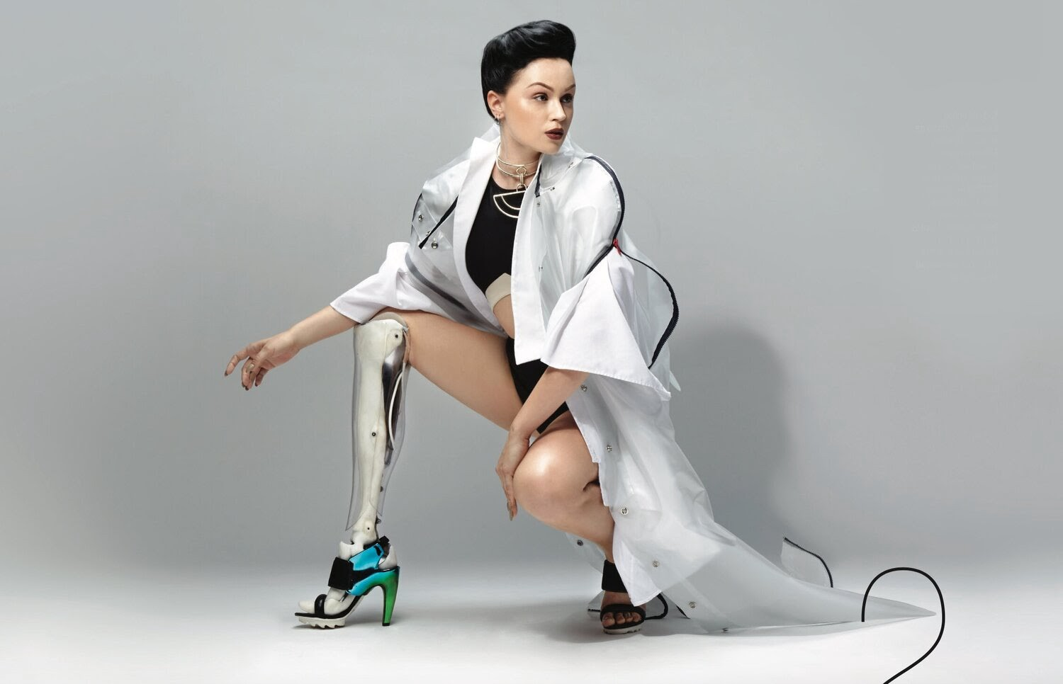 Cyborg Artist Viktoria Modesta crouching down showing off her metal leg in a heel, wearing a long white trench coat