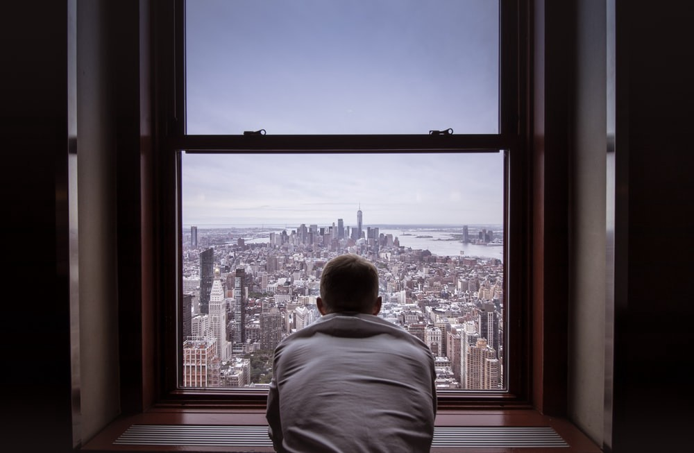A man in a grey hoodie looking from his window in the distance on New York city in America