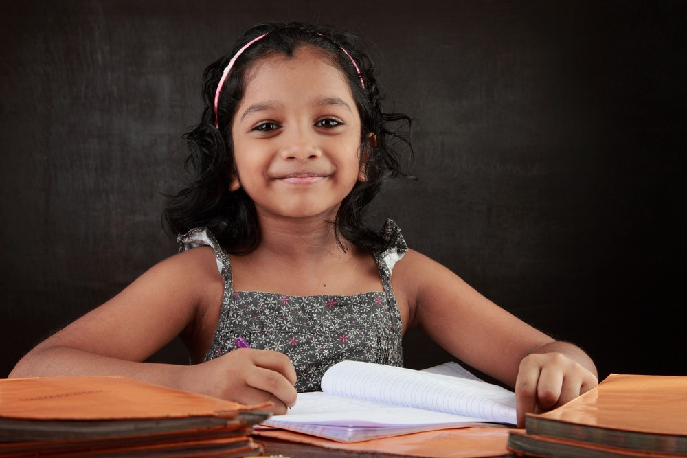 A little girl smiles as does her homework in the study room. The image indicate the investment option available for girl children.