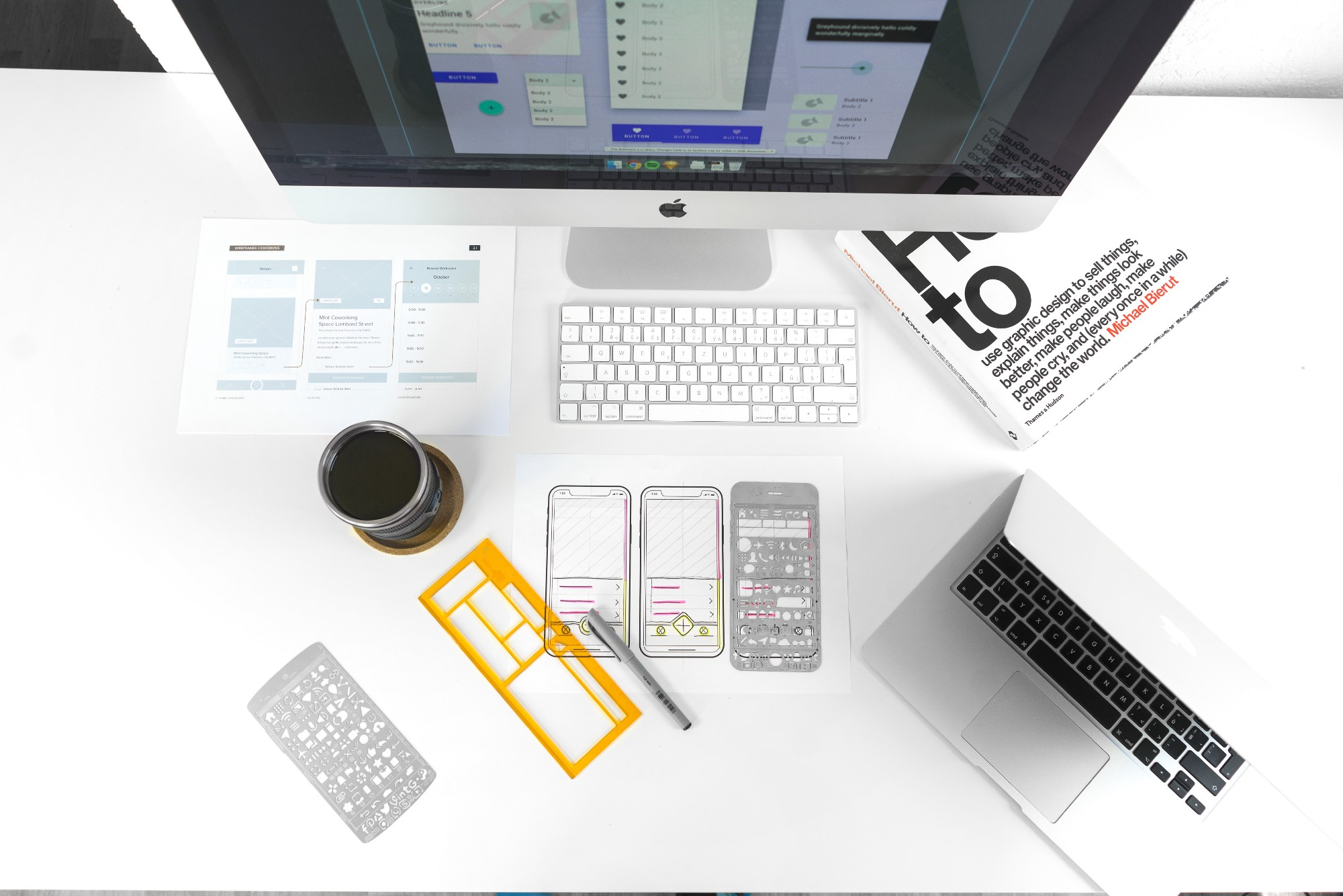 A bird's-eye view of a desk with an iMac, a MacBookPro, and papers scattered across the table.