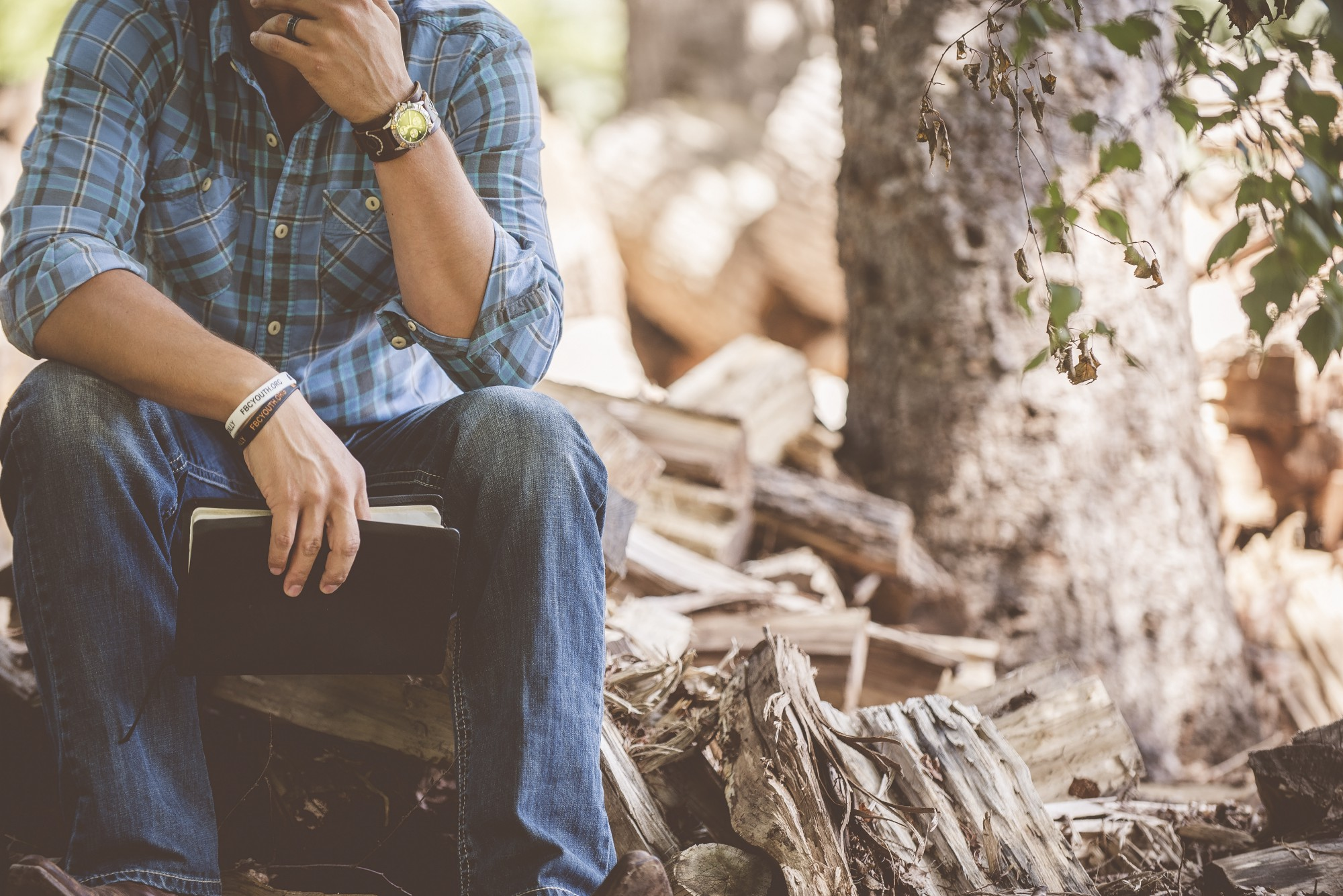 A white man sitting on a log next to a tree, holding a Bible. His other hand is touching his chin. His head is out of frame.