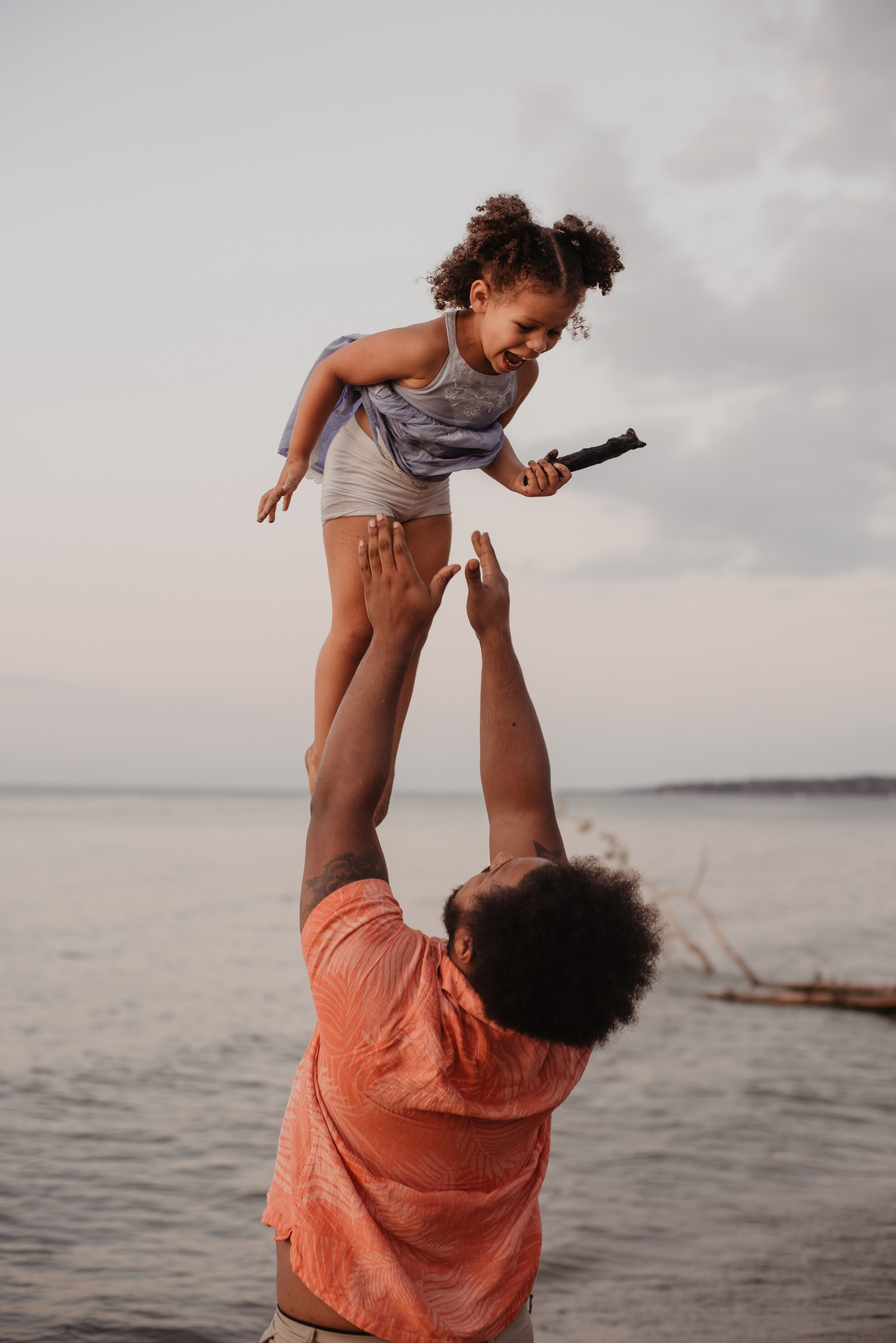 Image of a happy little girl being lifted in the air by her dad at the beach.