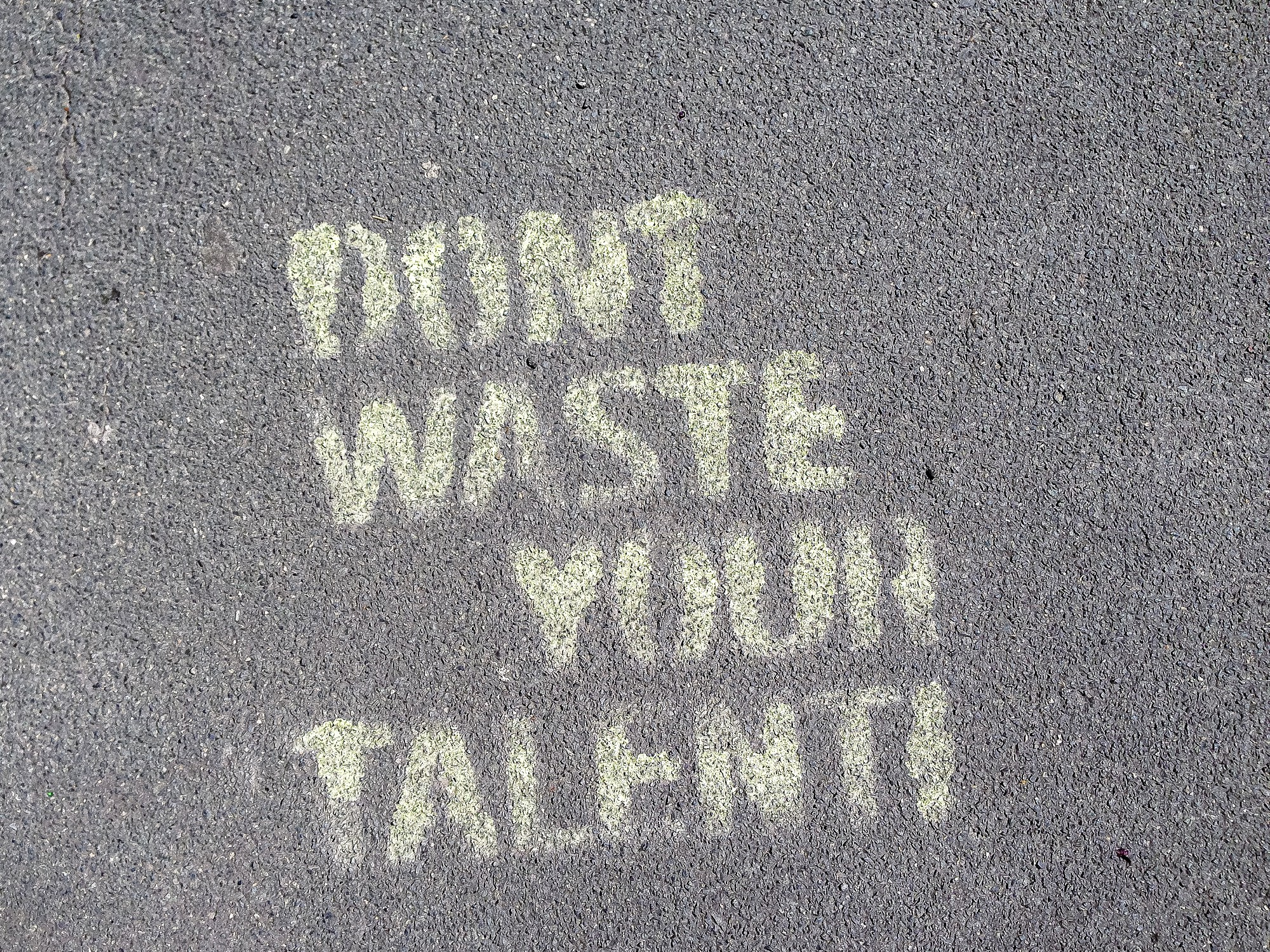 """Don't waste your talent"" written in chalk on pavement"
