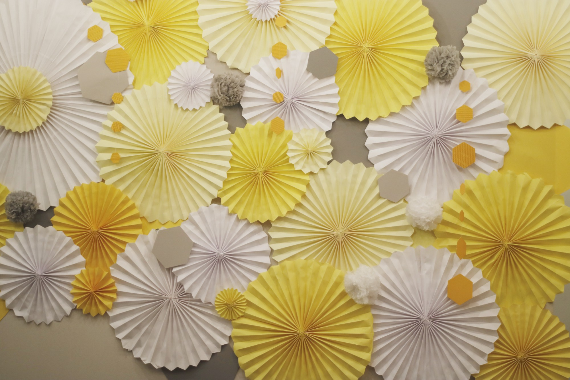 a display of accordion fold paper flowers (or possibly the tops of umbrellas) in shades of yellow
