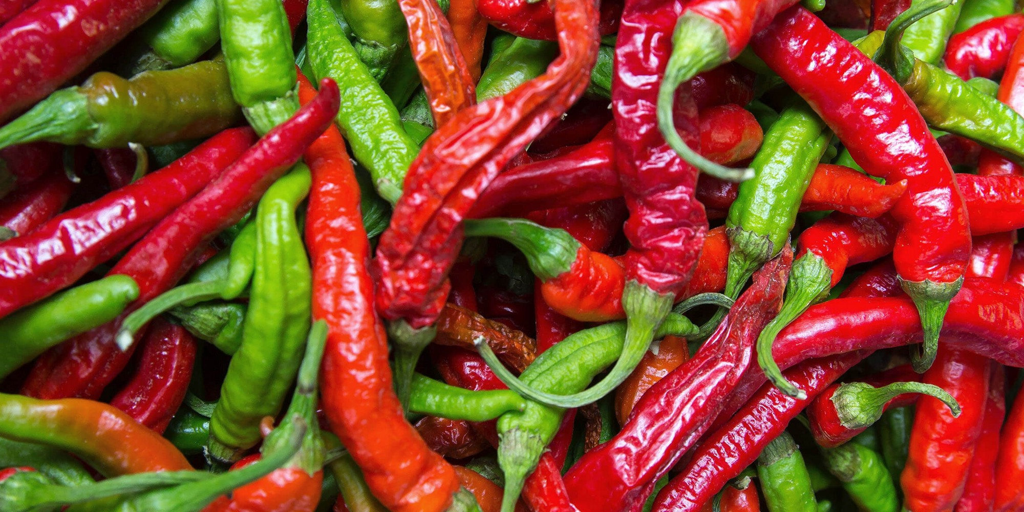 A photograph showing a mixture of red and green chili peppers