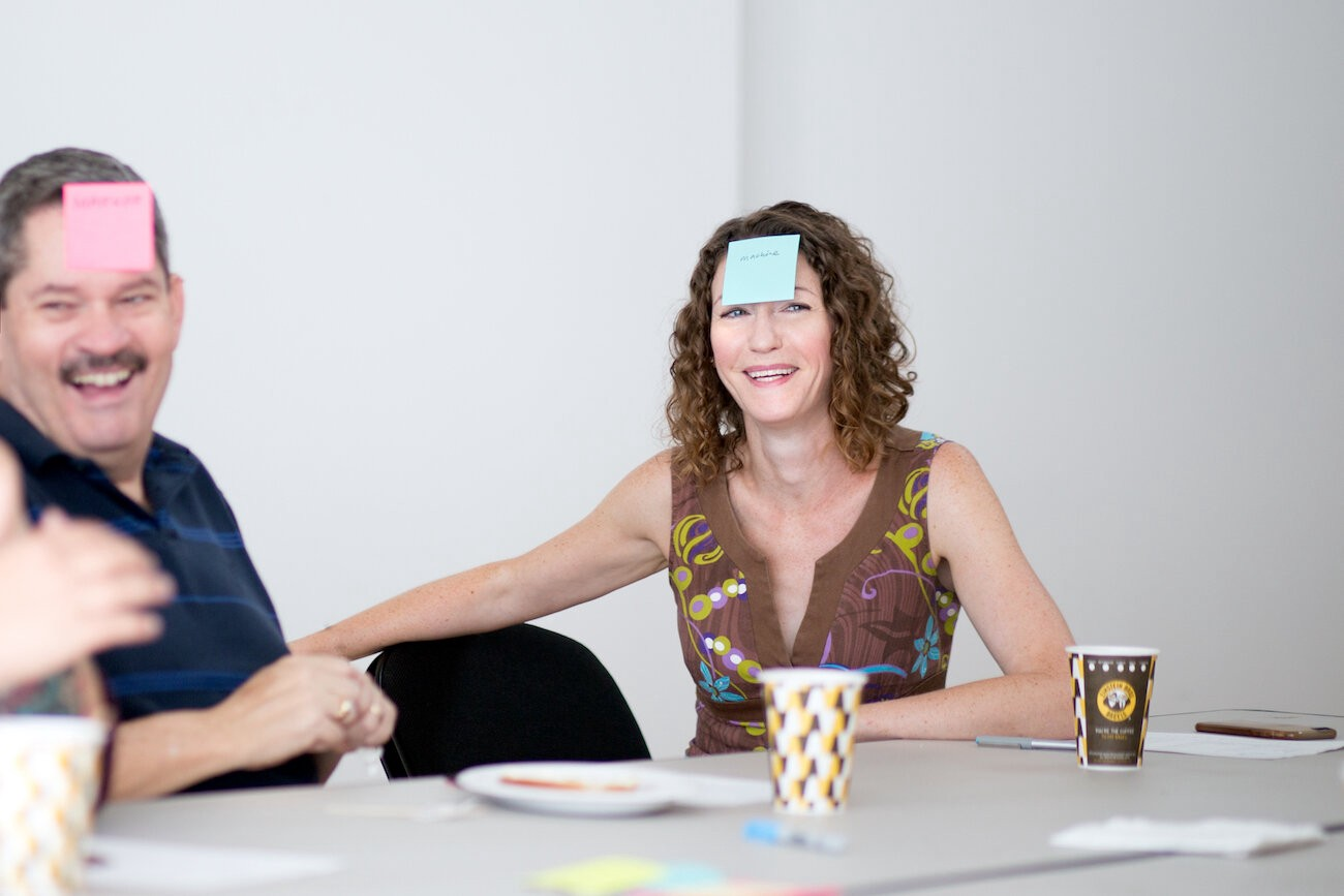 Team meeting with a man and a woman smiling, with sticky notes on their foreheads