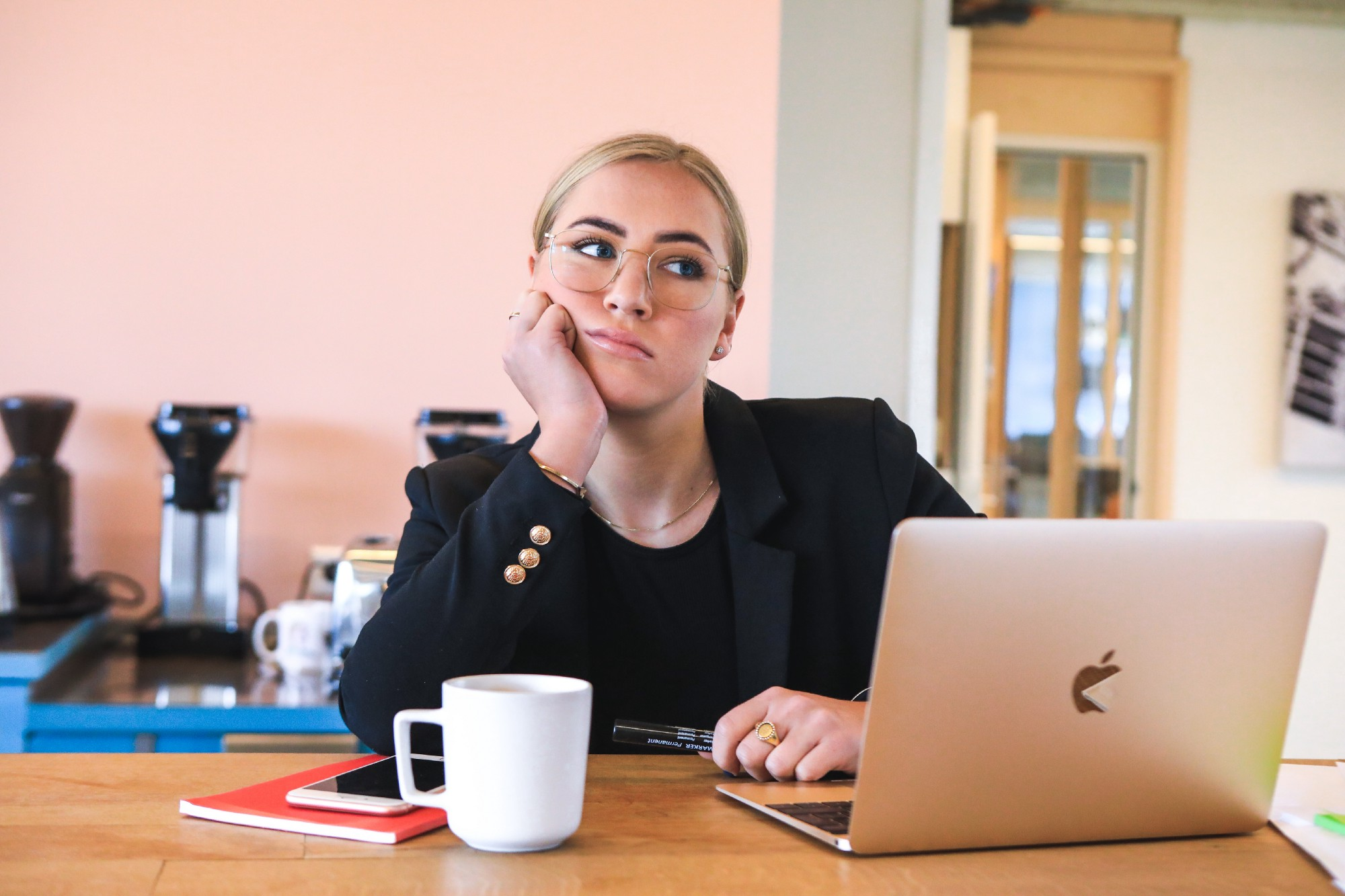 woman with glasses and pantsuit at table with coffee and laptop, head leaning on hand, thinking look.