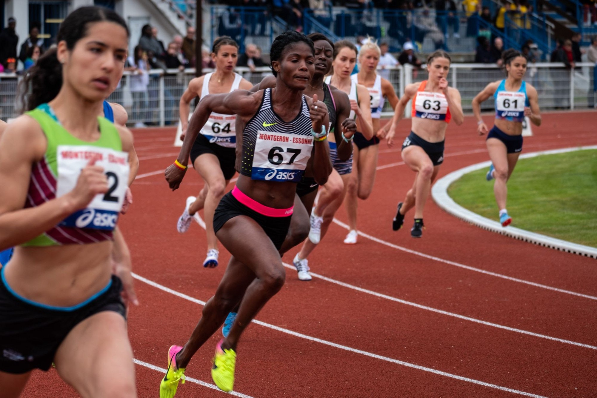 Female runners in a track competition running around a curve in the track.