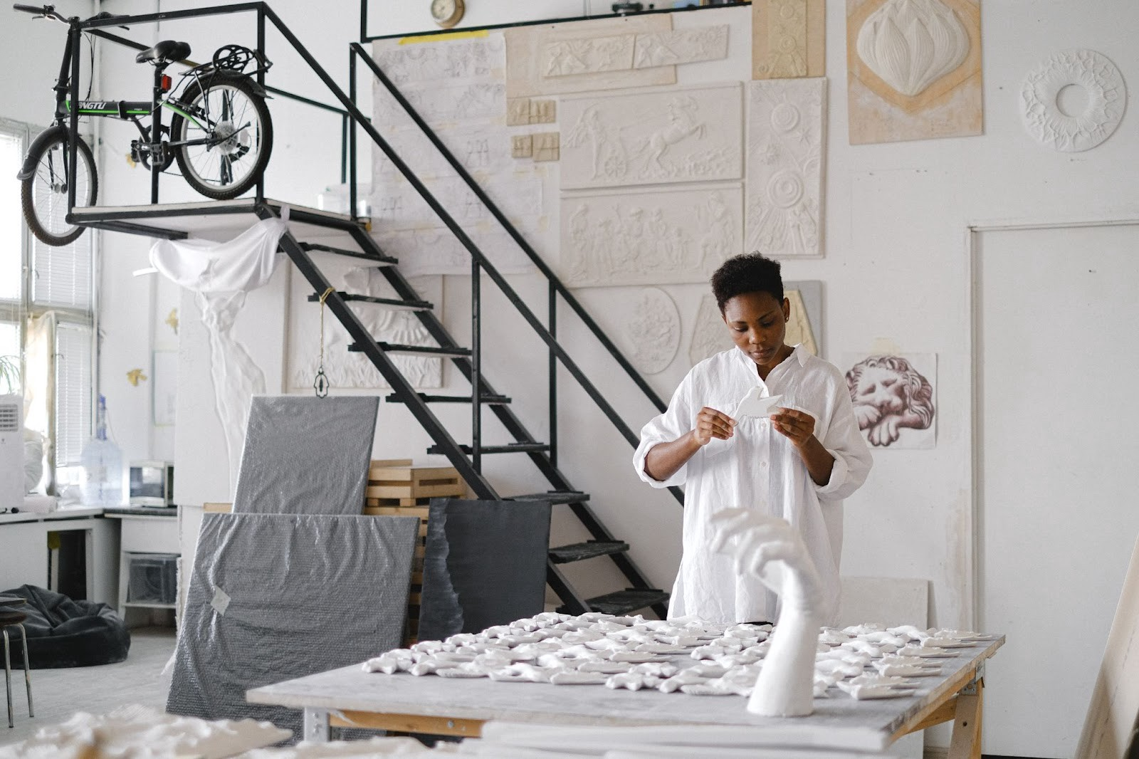 Woman in a white art studio, wearing a white dress and hold a piece of plaster shaped like a bird. The table infront is full of plaster mouldings and the walls are covered in flat sculptures.