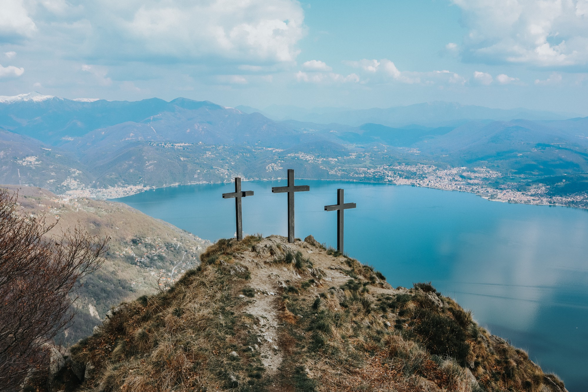 Three crosses on a sandy mountain overlooking a large body of bright blue water on a sunny day.