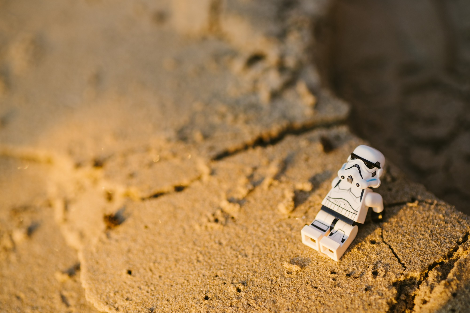 Lego storm trooper sitting in the sand while contemplating life.