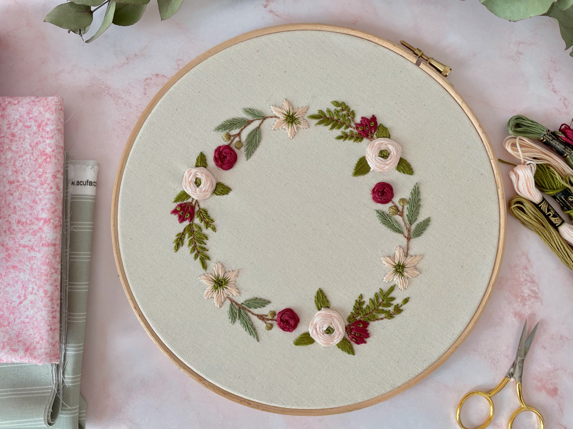 An embroidery hoop with a flower wreath stitched on it, on a pink marble table with embroidery thread next to it.