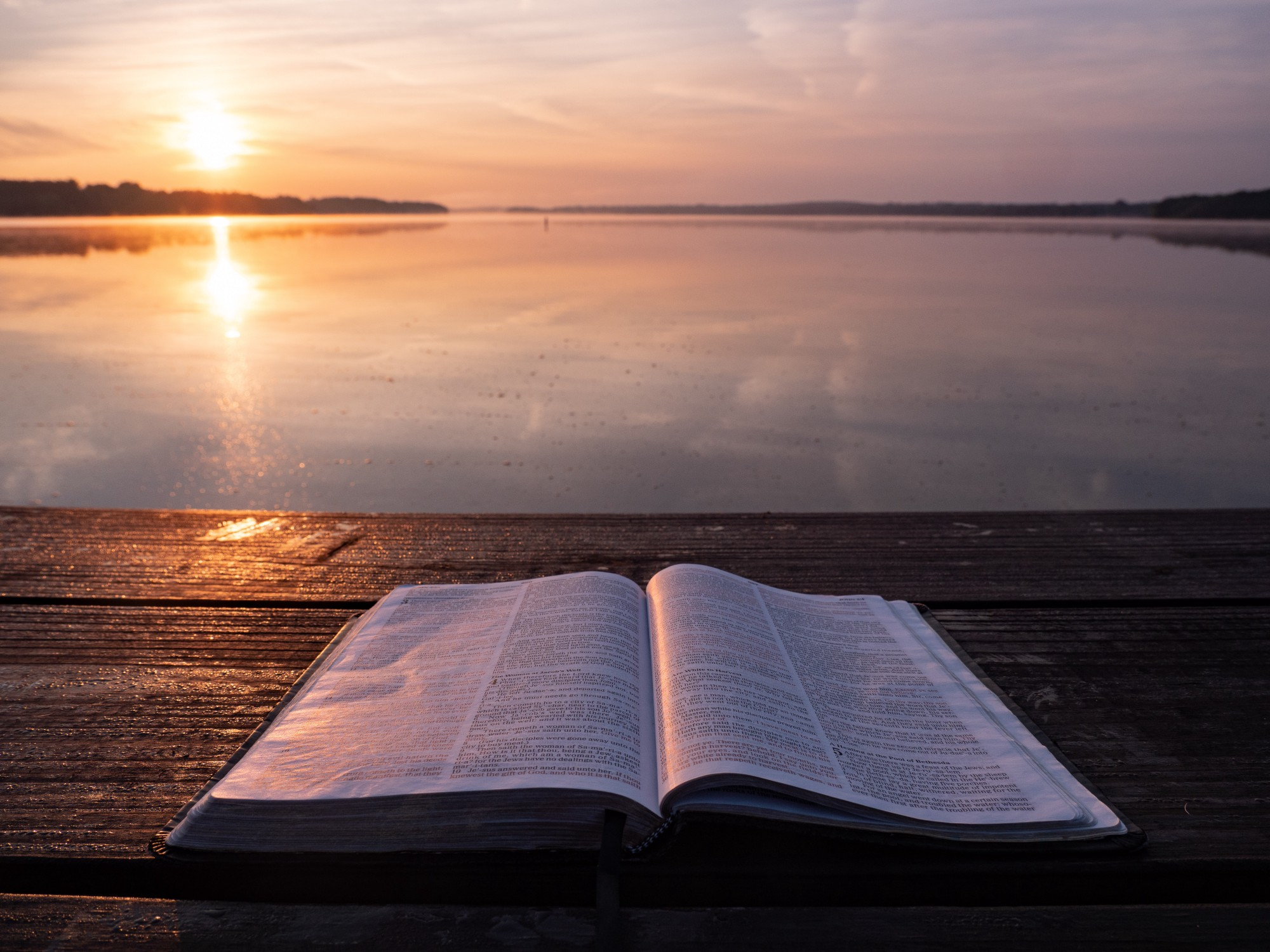 Open Bible on deck next to lake with thin horizon line in the distance golden sun reflecting on the water and deck on left.